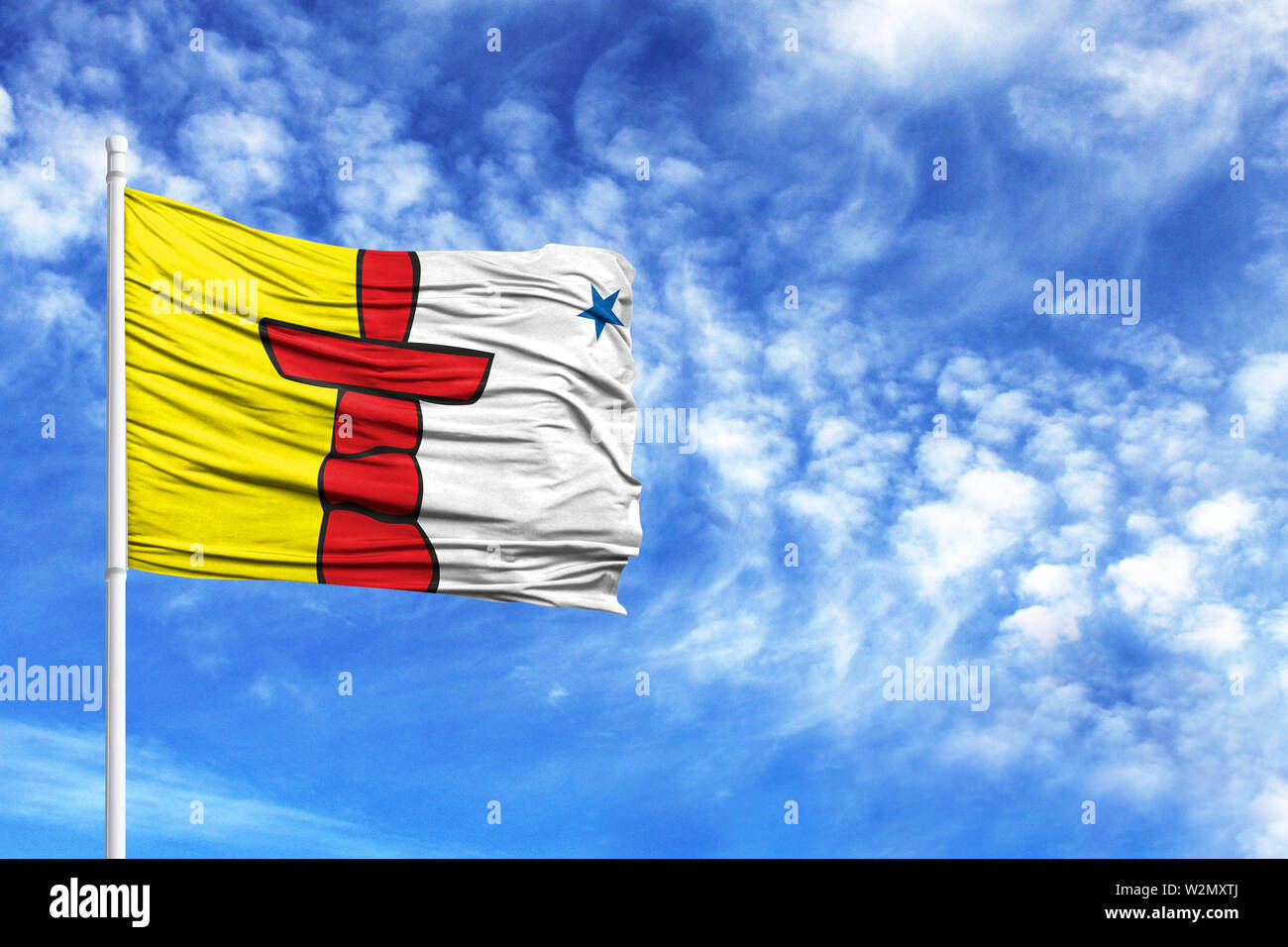 National flag of Nunavut on a flagpole in front of blue sky - Stock Image