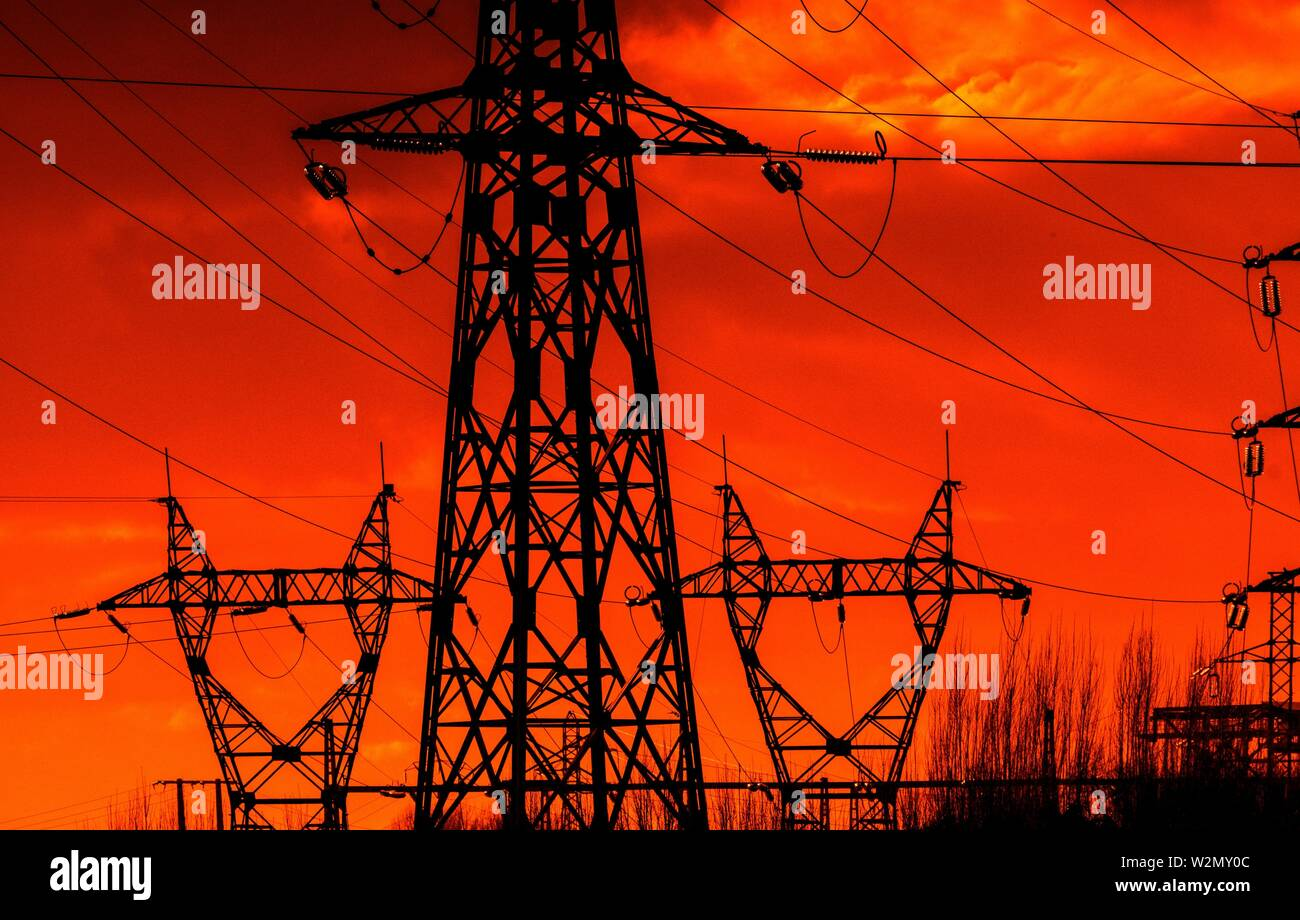 Electricity pylons at sunset, orange sky - Stock Image