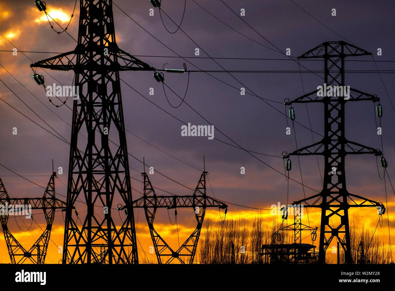 Electricity pylons at sunset - Stock Image