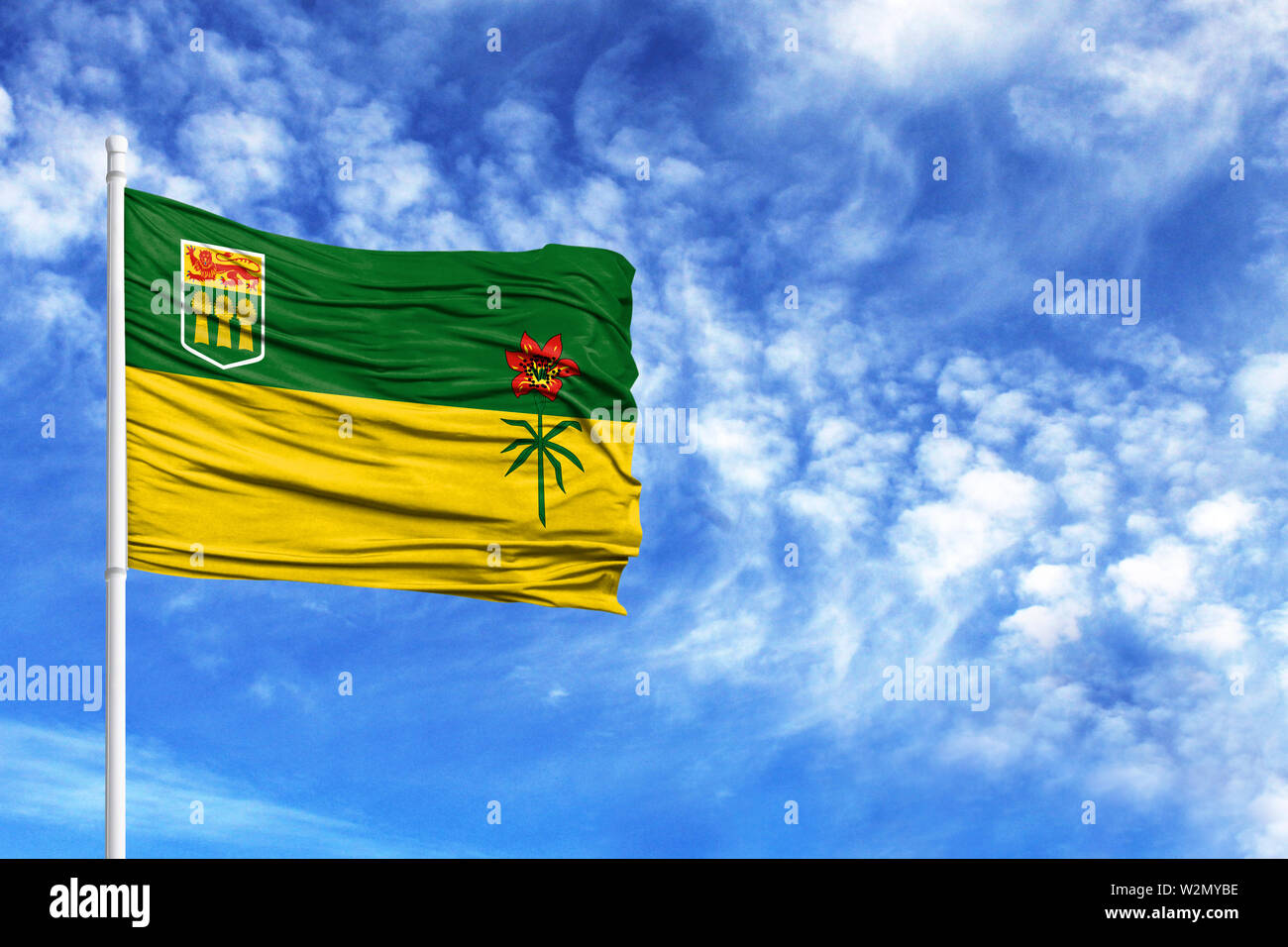 National flag of Saskatchewan on a flagpole in front of blue sky - Stock Image