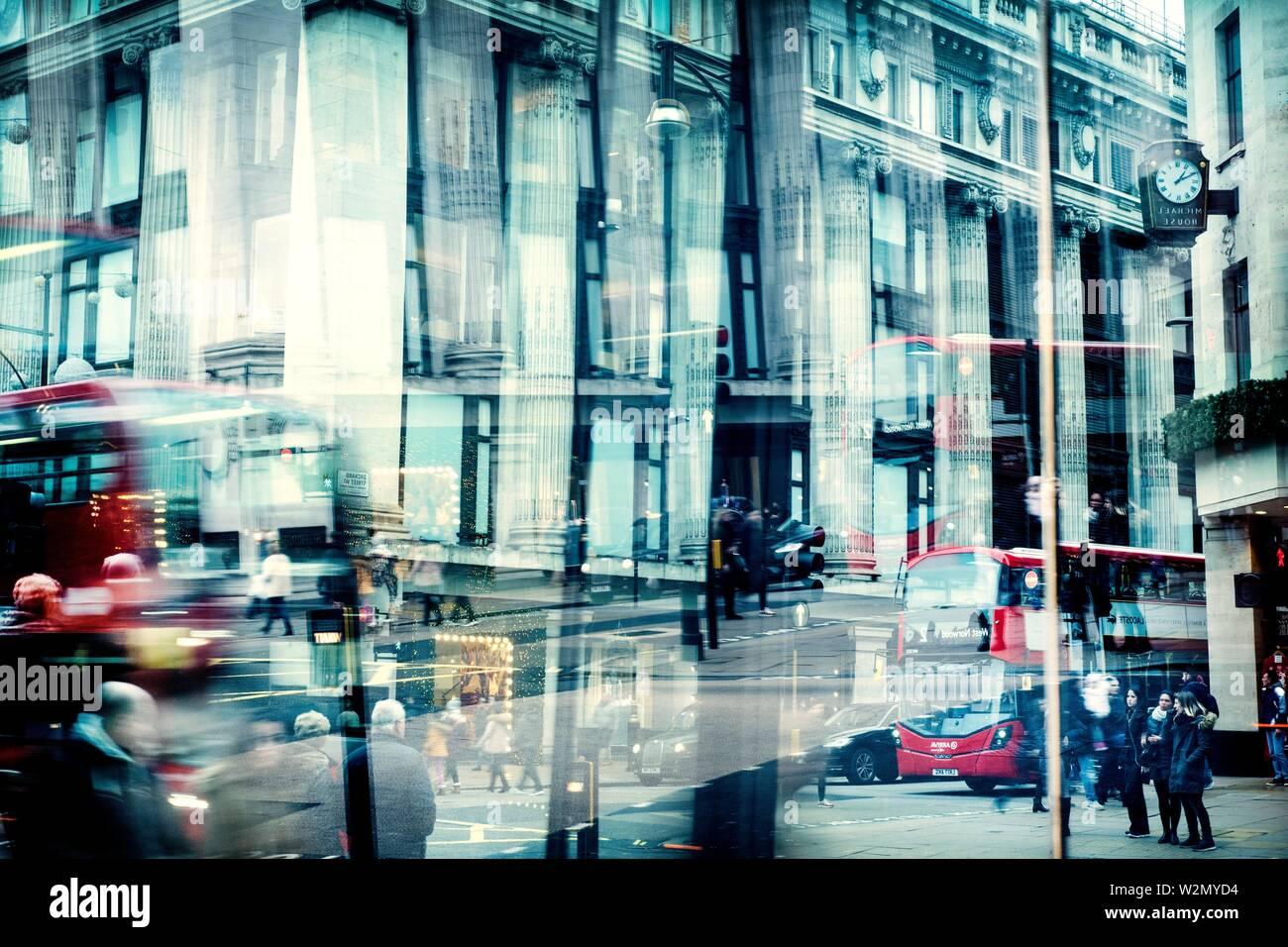 View of a street reflected in a glass with traffic, people and buildings. Selfridges, Oxford St. Londes, UK, Europe. - Stock Image