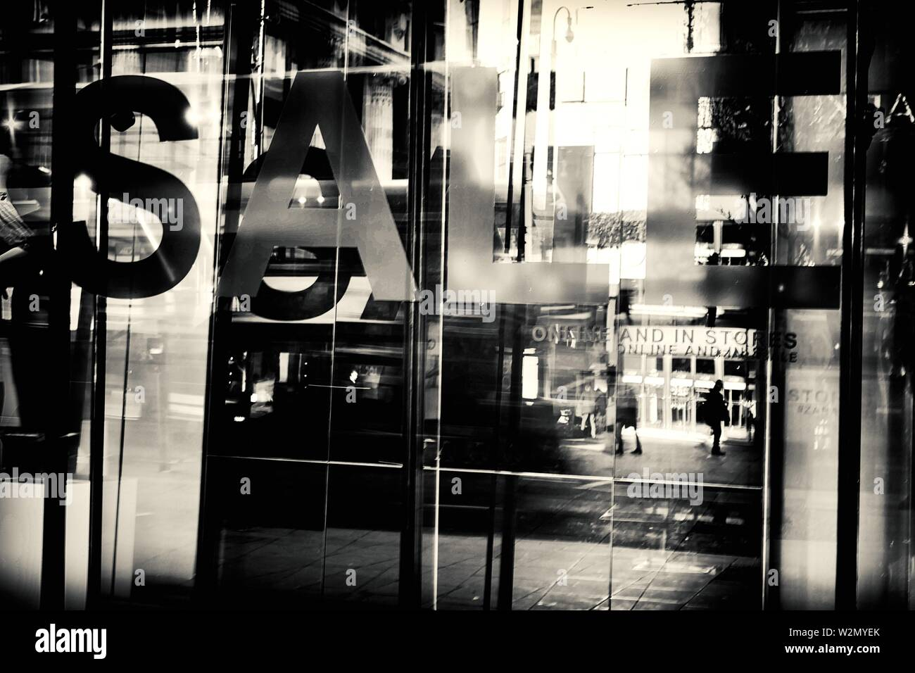View of a street reflected in a glass with traffic, people and SALE written on glass.Oxford St. Londes, UK, Europe. - Stock Image