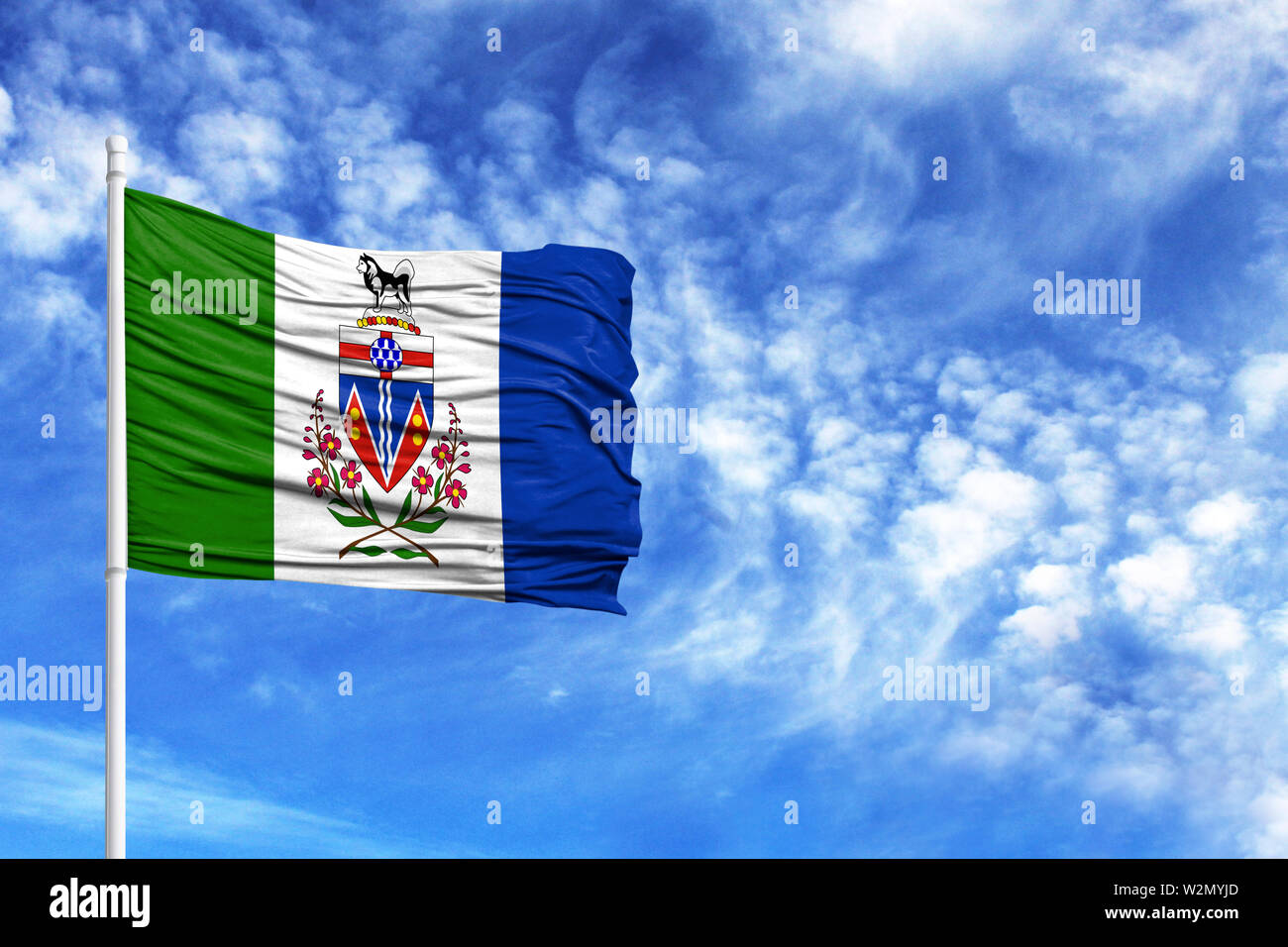 National flag of Yukon on a flagpole in front of blue sky - Stock Image