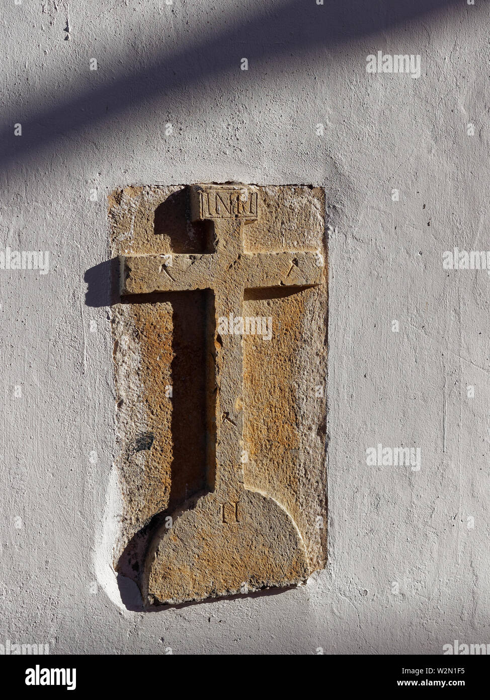 A Carved Stone Cross embedded into the Walls of a House in a street of the Portuguese Town of Estoi on the Algarve on a hot Summers afternoon. Portuga Stock Photo