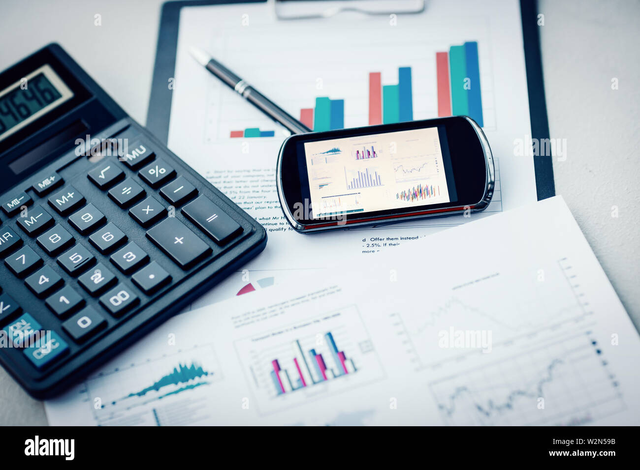 close up  calculator, mobile phone and financial charts on