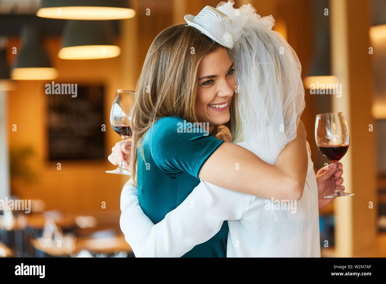 Bride hugs her best friend at hen party in the restaurant - Stock Image