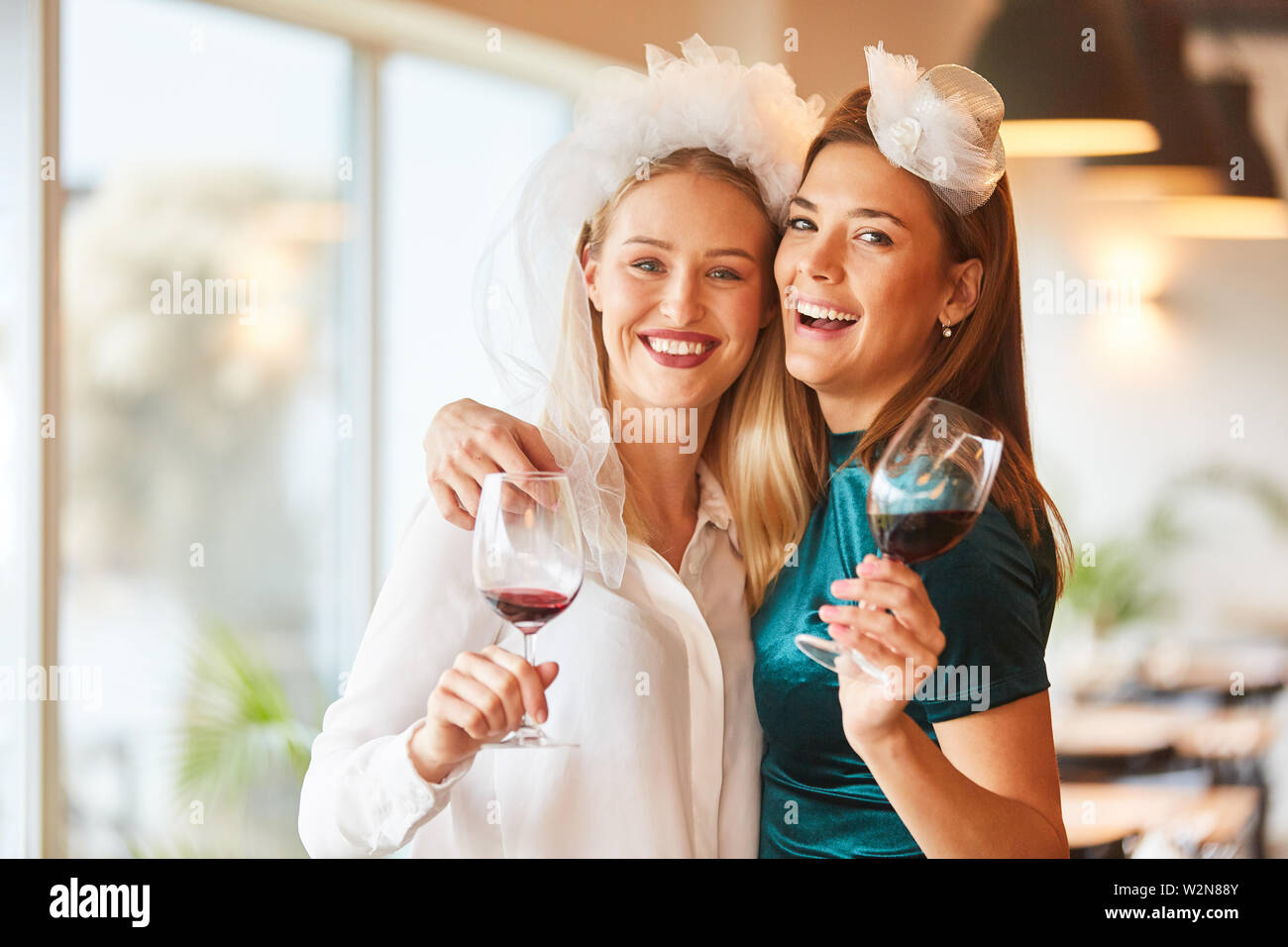 Happy bride is celebrating with her best friend on the bachelorette party - Stock Image