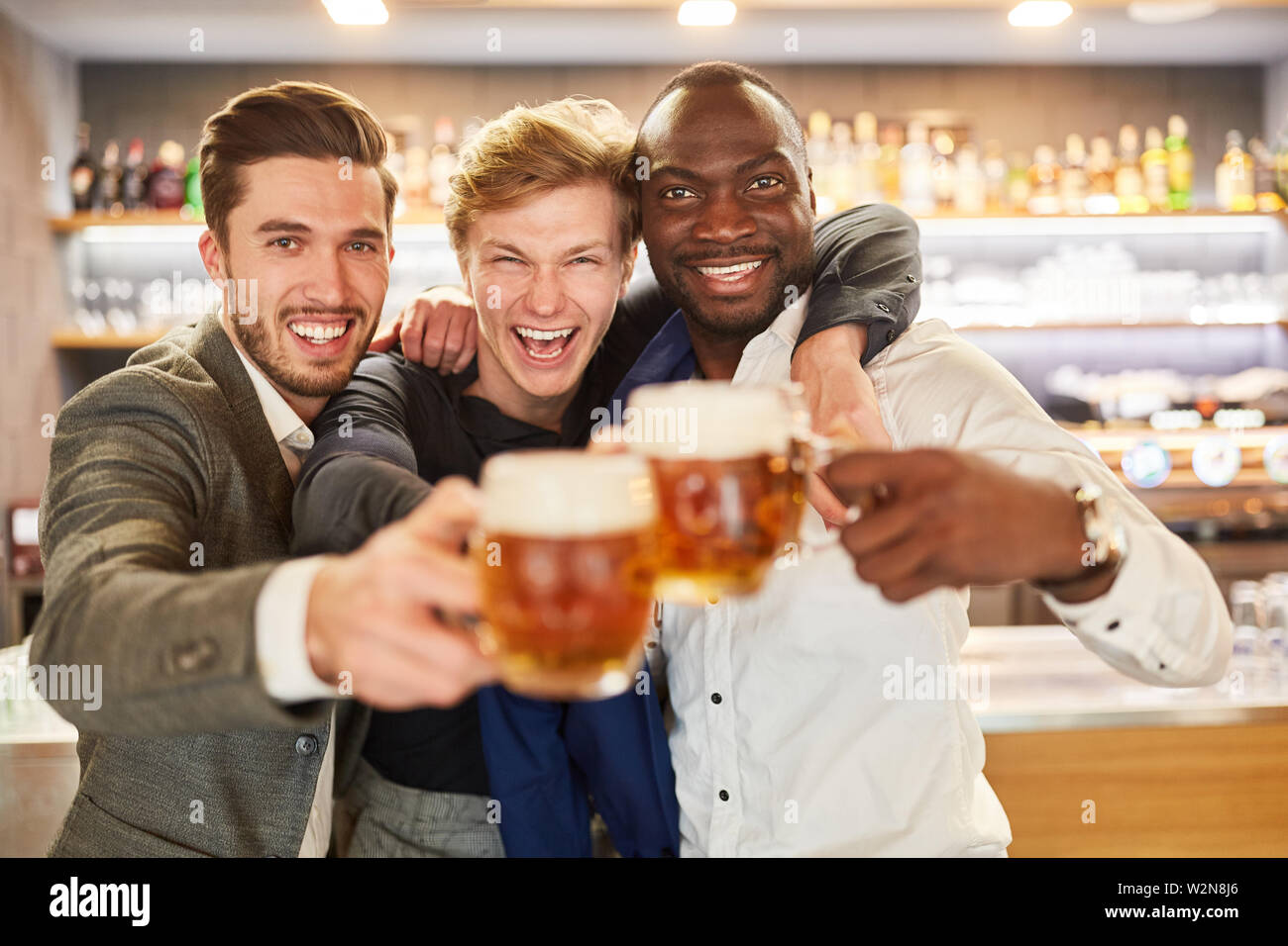 Three men as best friends celebrate hilariously with beer on a pub crawl - Stock Image