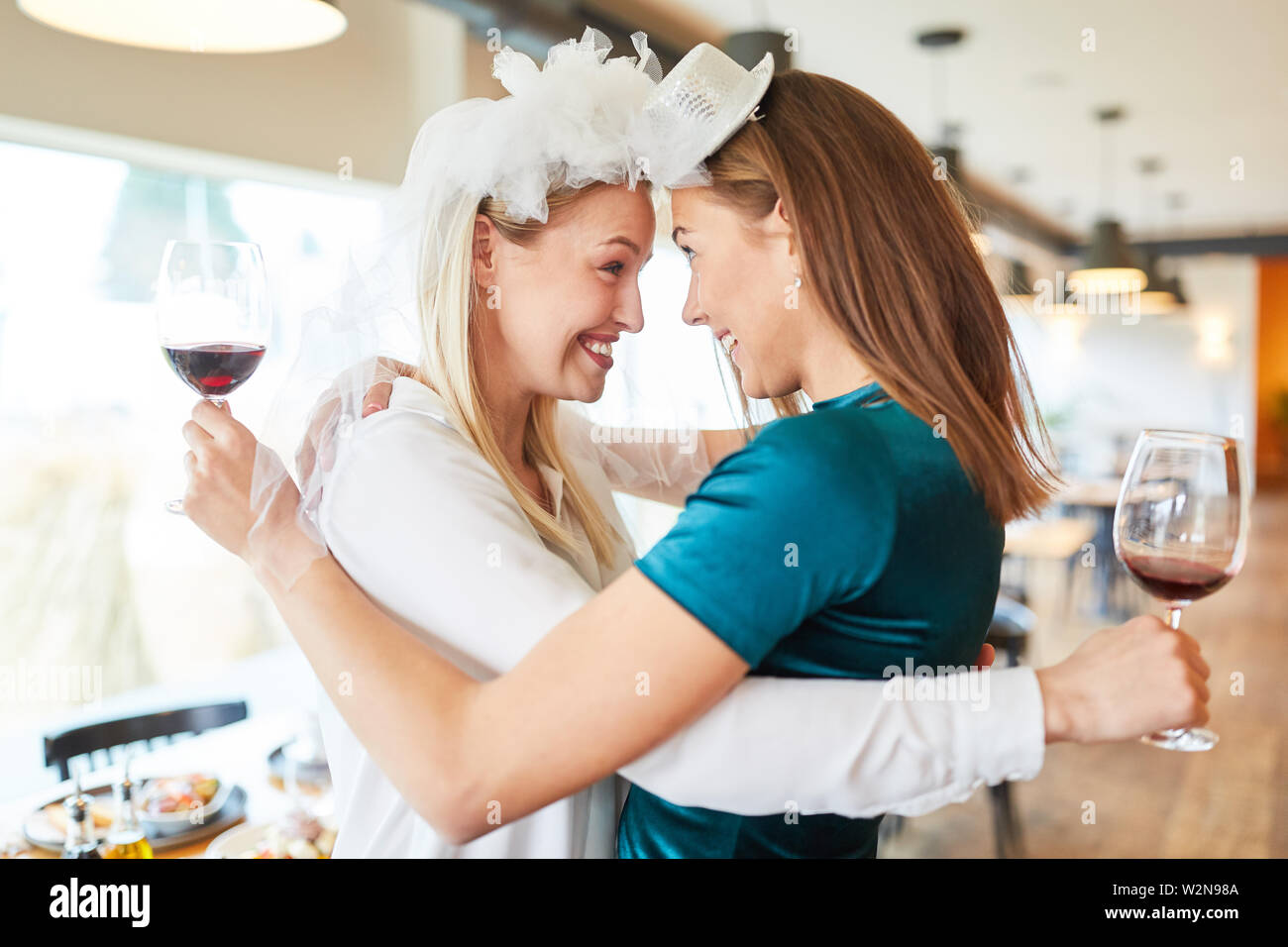 Happy young woman with bridal veil hugs her best friend in the restaurant - Stock Image