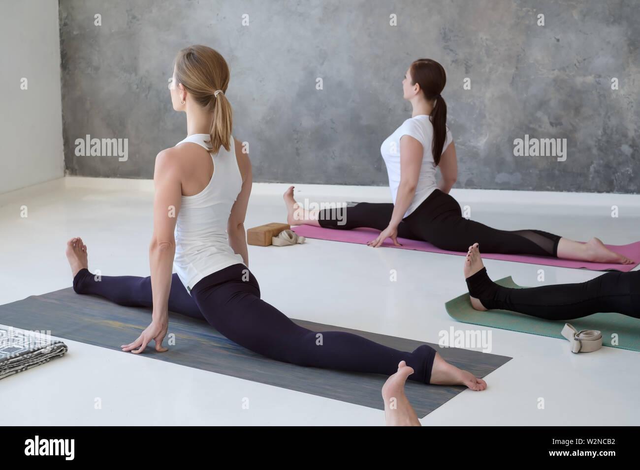 Sporty caucasian people doing yoga Hanumanasana pose, working out indoor - Stock Image
