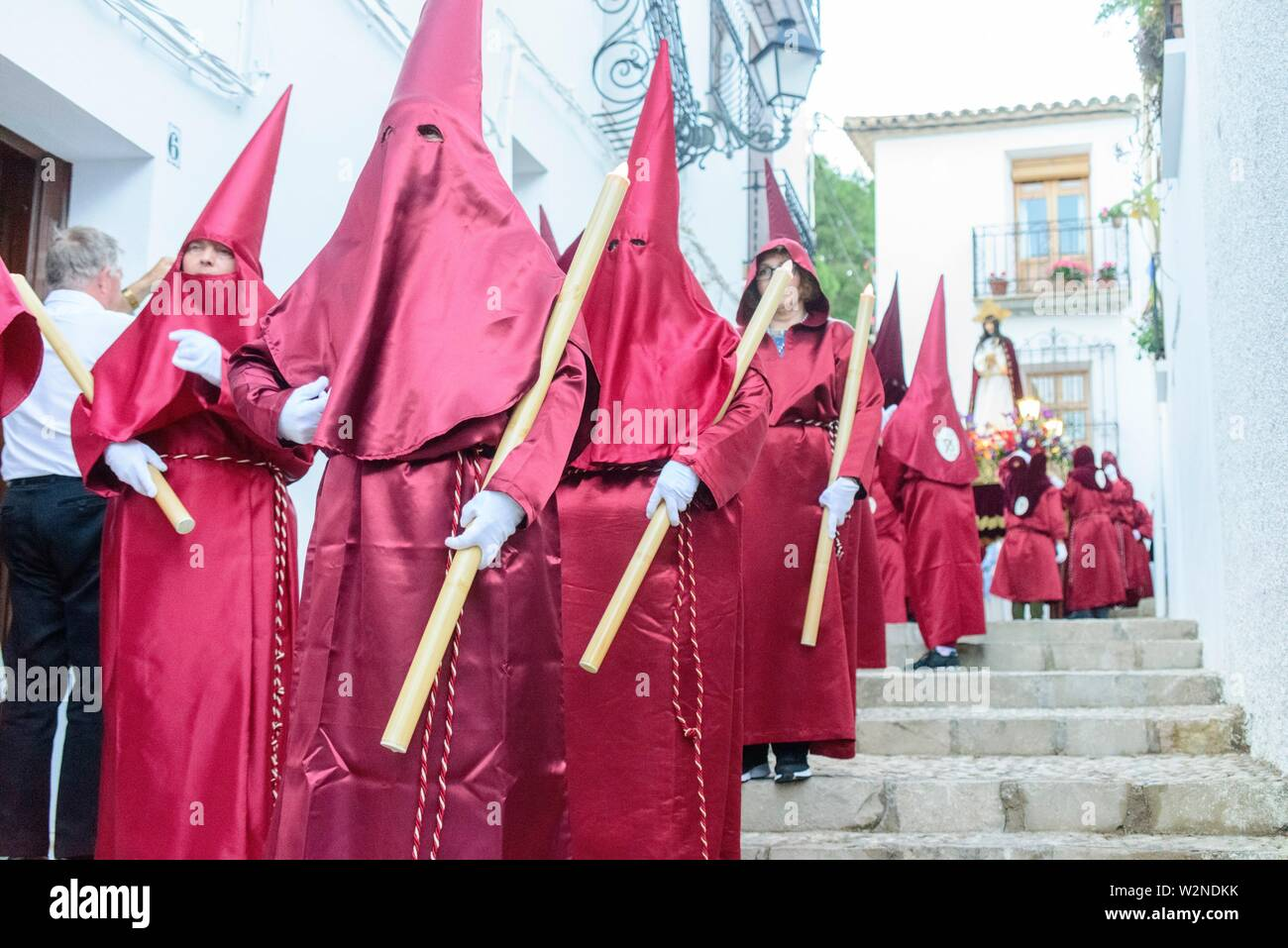 Cofrades with the tunic and the red procession cap through the streets of Altea - Stock Image