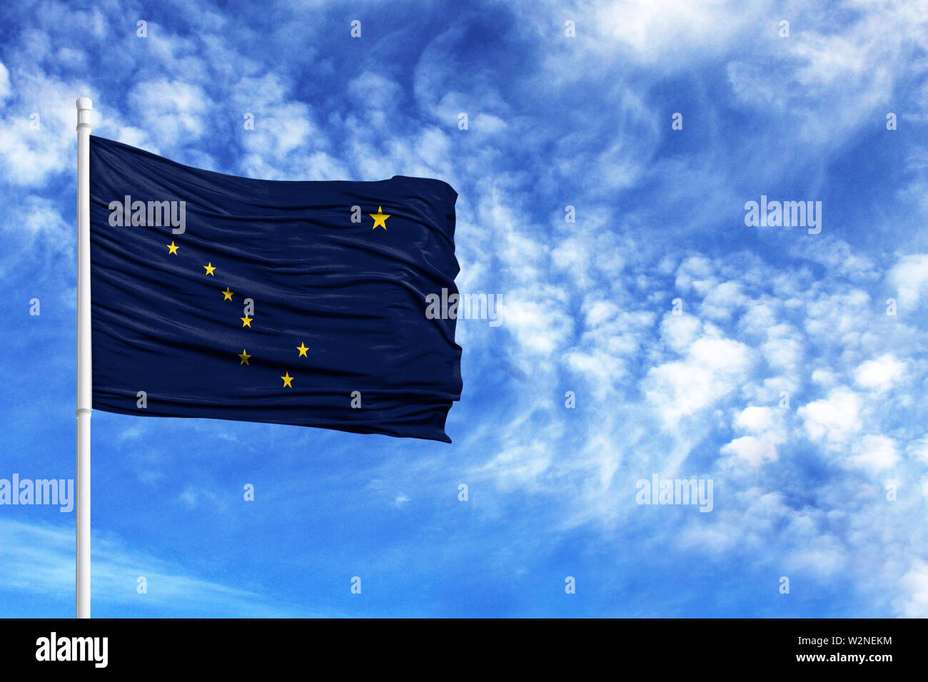 National flag State of Alaska on a flagpole in front of blue sky - Stock Image