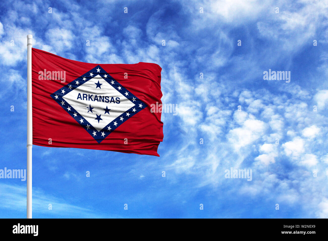 National flag State of Arkansas on a flagpole in front of blue sky - Stock Image