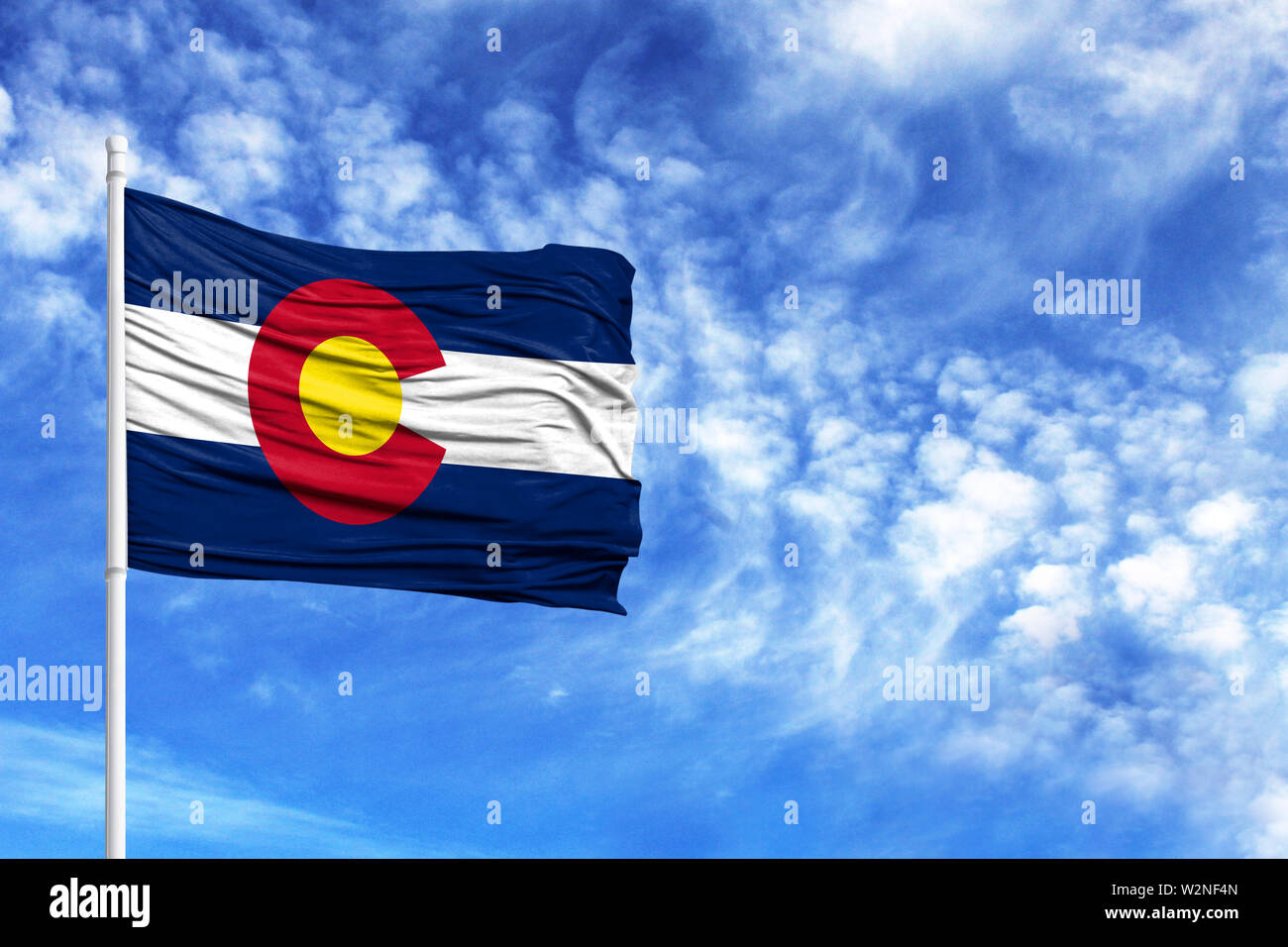 National flag State of Colorado on a flagpole in front of blue sky - Stock Image