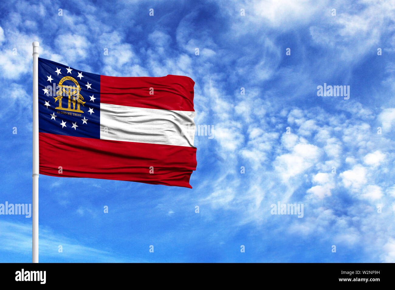 National flag State of Georgia on a flagpole in front of blue sky - Stock Image