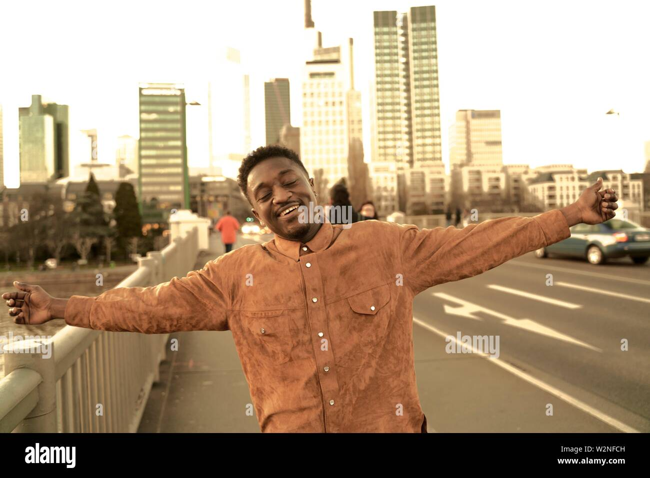 eased African man with open arms at street in city, carefree, in Frankfurt, Germany. Stock Photo