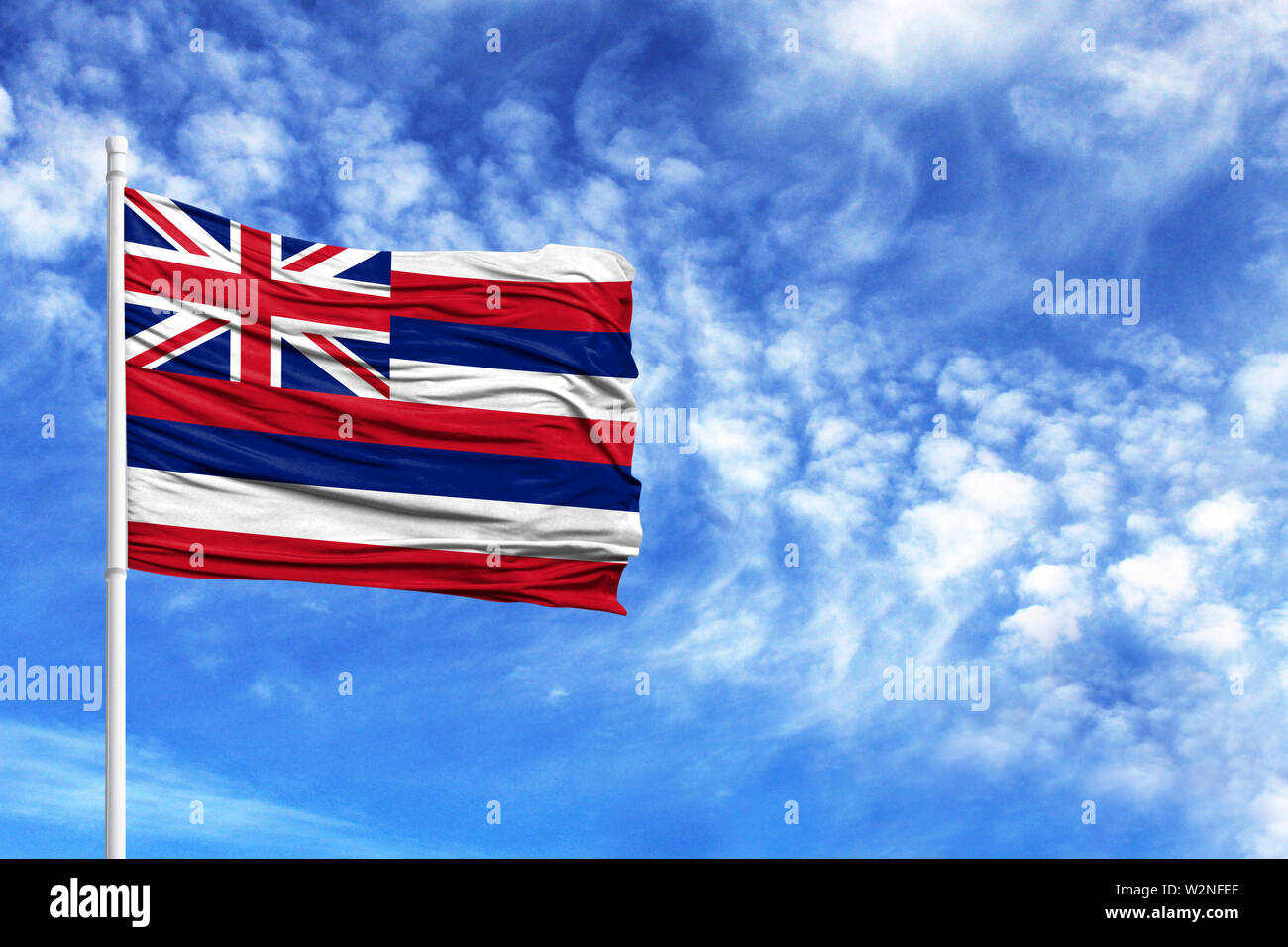 National flag State of Hawaii on a flagpole in front of blue sky - Stock Image
