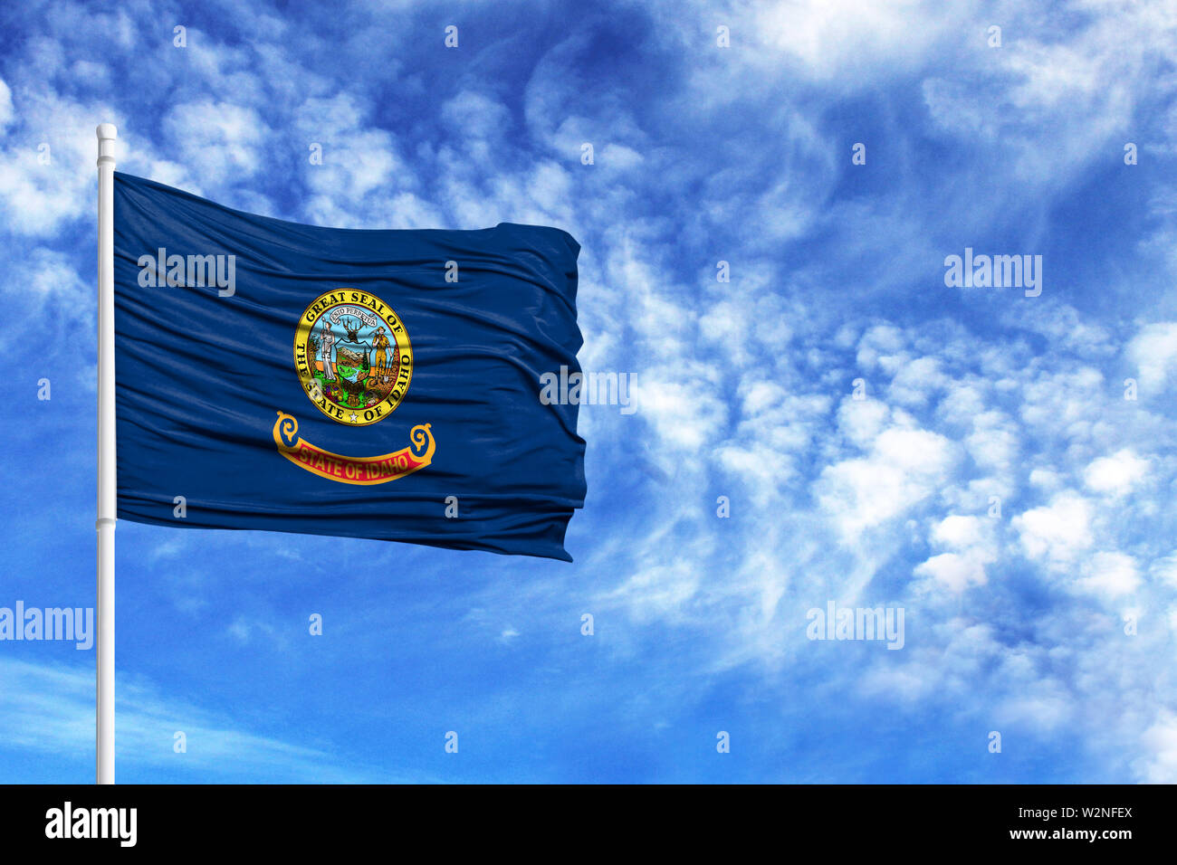 National flag State of Idaho on a flagpole in front of blue sky - Stock Image