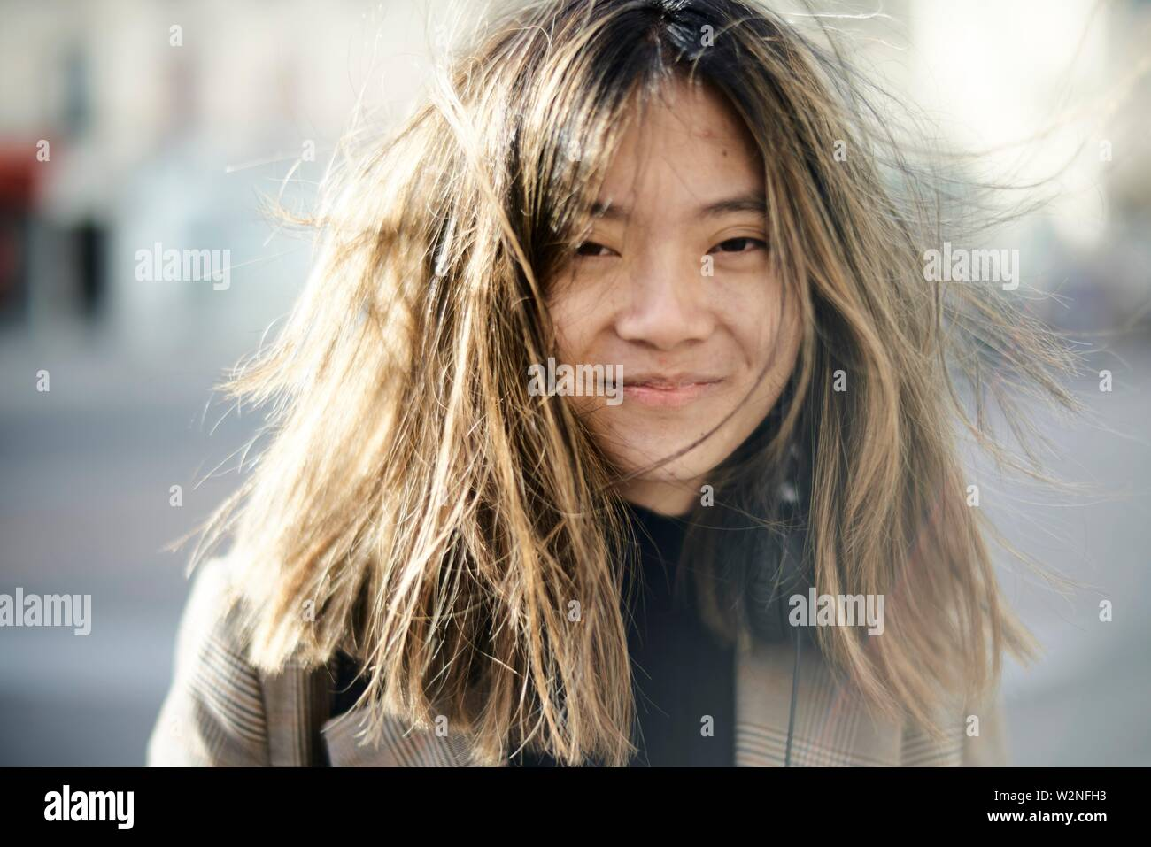 young unkempt Asian woman with tousled hairs, bad hair day, in Paris, France. - Stock Image