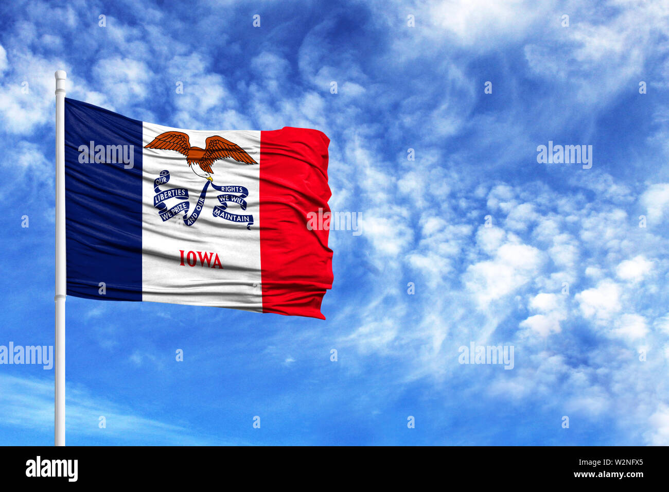 National flag State of Iowa on a flagpole in front of blue sky - Stock Image