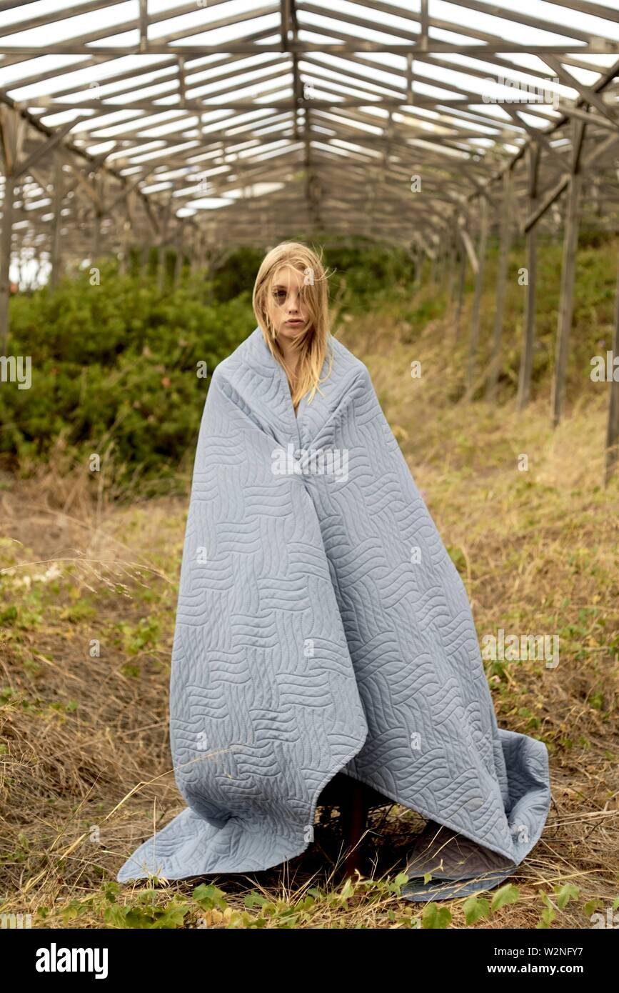 young defaced teenage woman with black eye standing in abandoned greenhouse, scars, enrolled in blanket - Stock Image