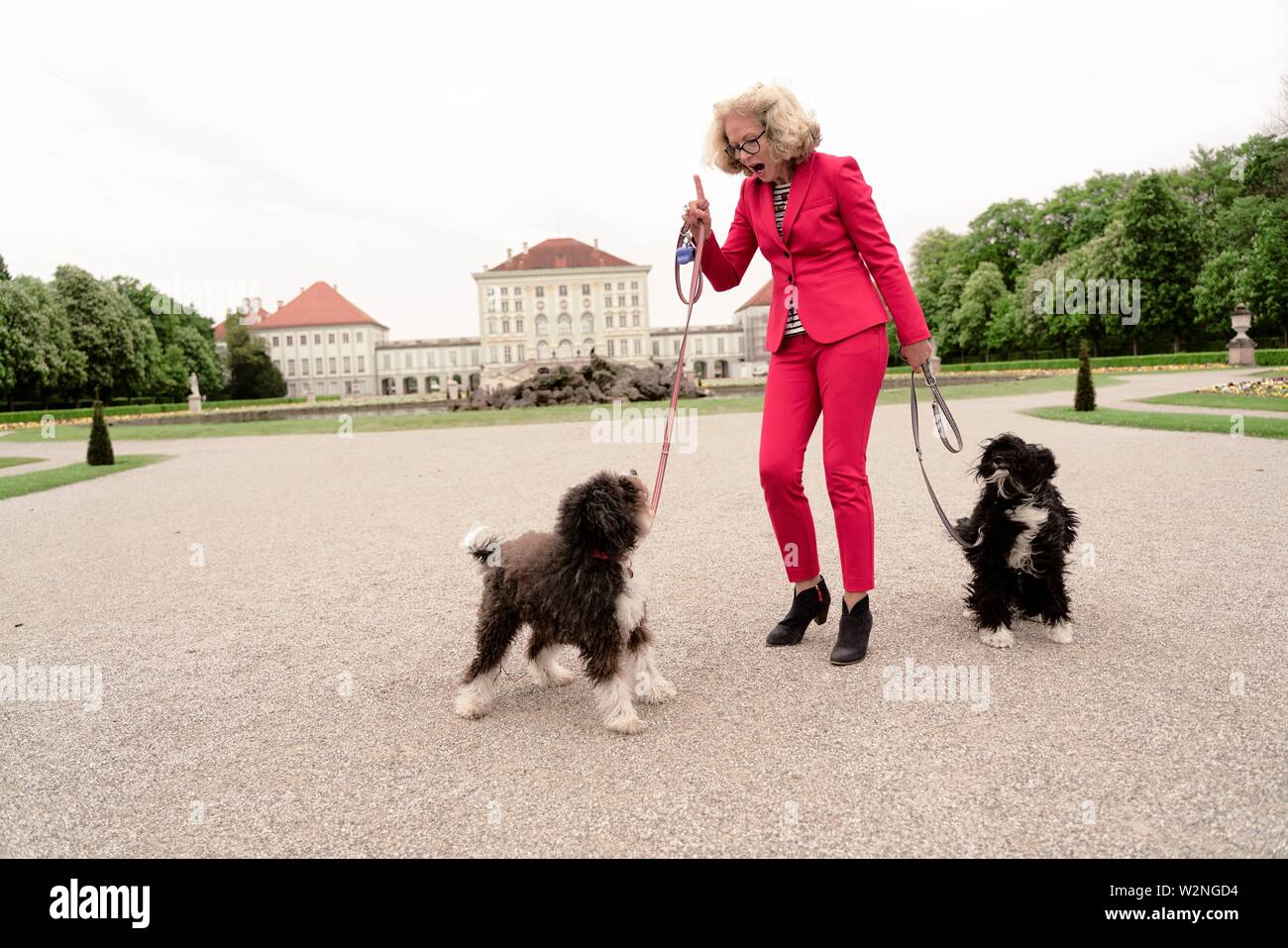 senior woman with her dogs in park, next to Nymphenburg palace, in Munich, Germany. - Stock Image