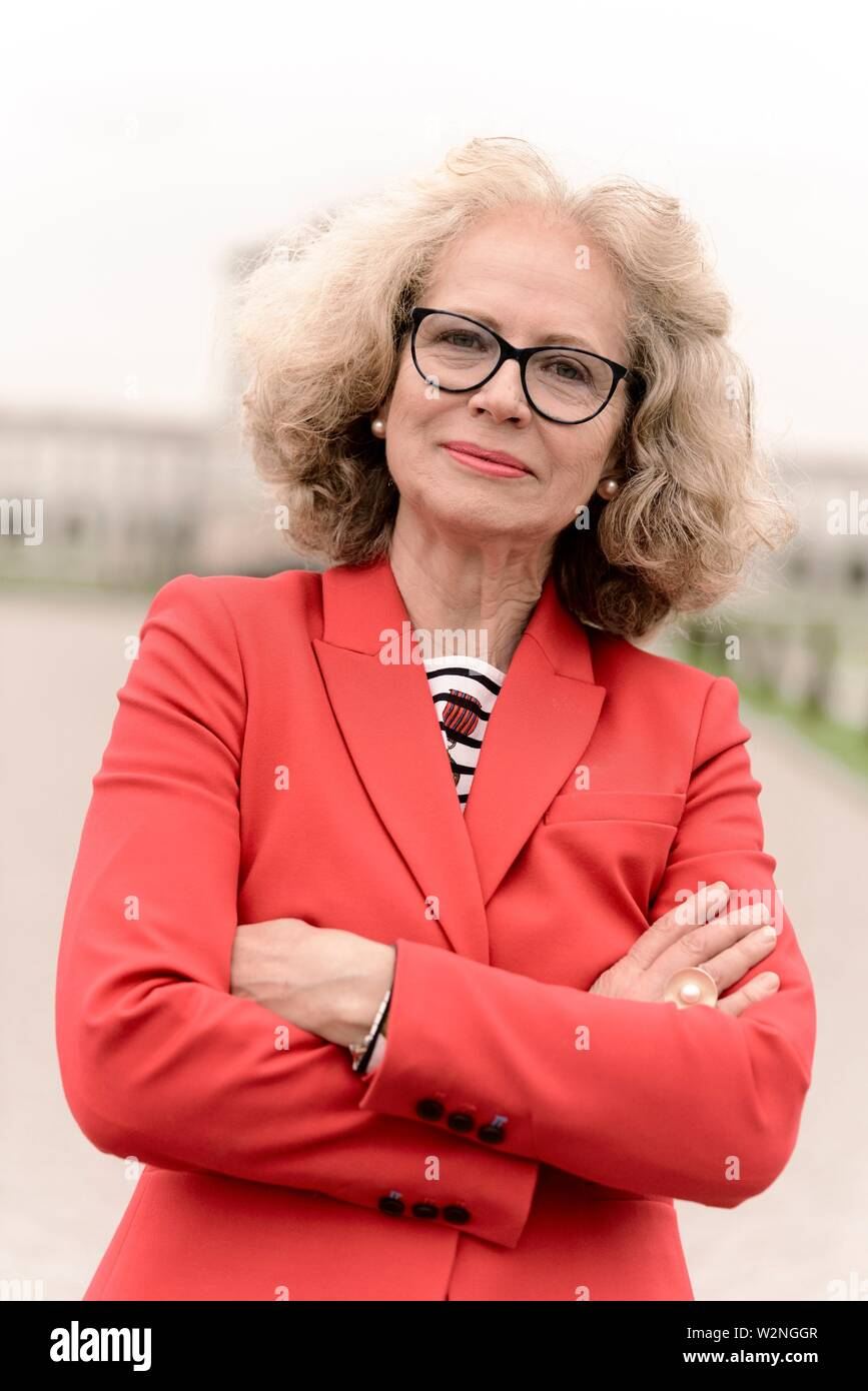 competent senior woman (67 years old) with crossed arms, in Nymphenburg, Munich, Germany. - Stock Image