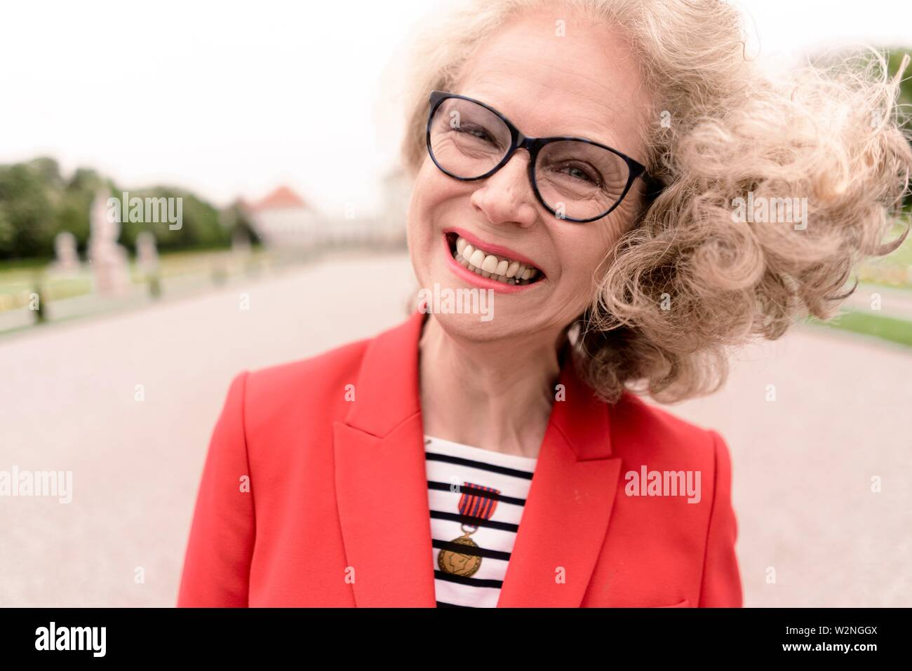 zestful senior woman (67 years old) in park, in Nymphenburg, Munich, Germany. - Stock Image