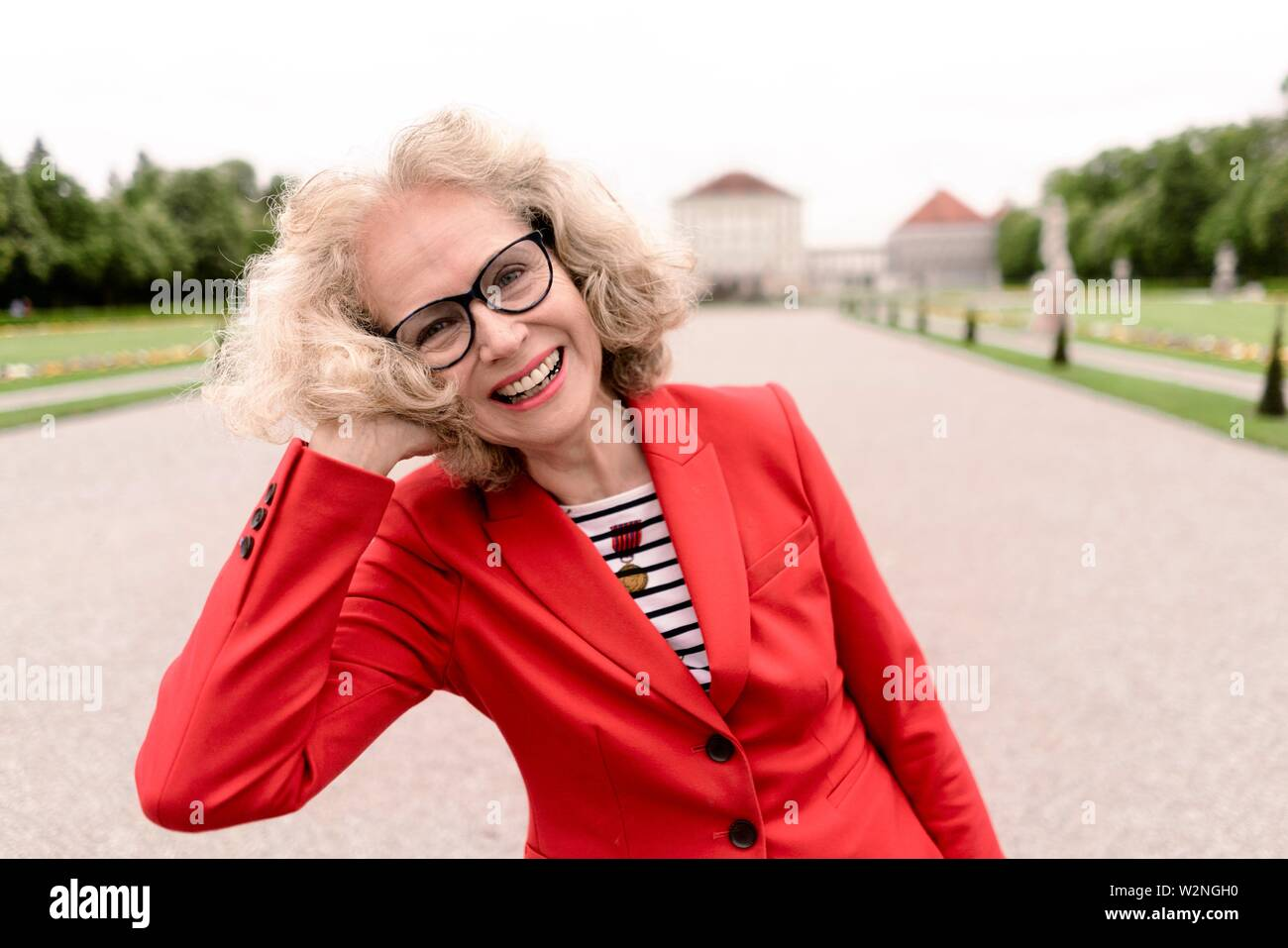 happy senior woman (67 years old) in park at touristic sight Nymphenburg palace, in Munich, Germany. - Stock Image