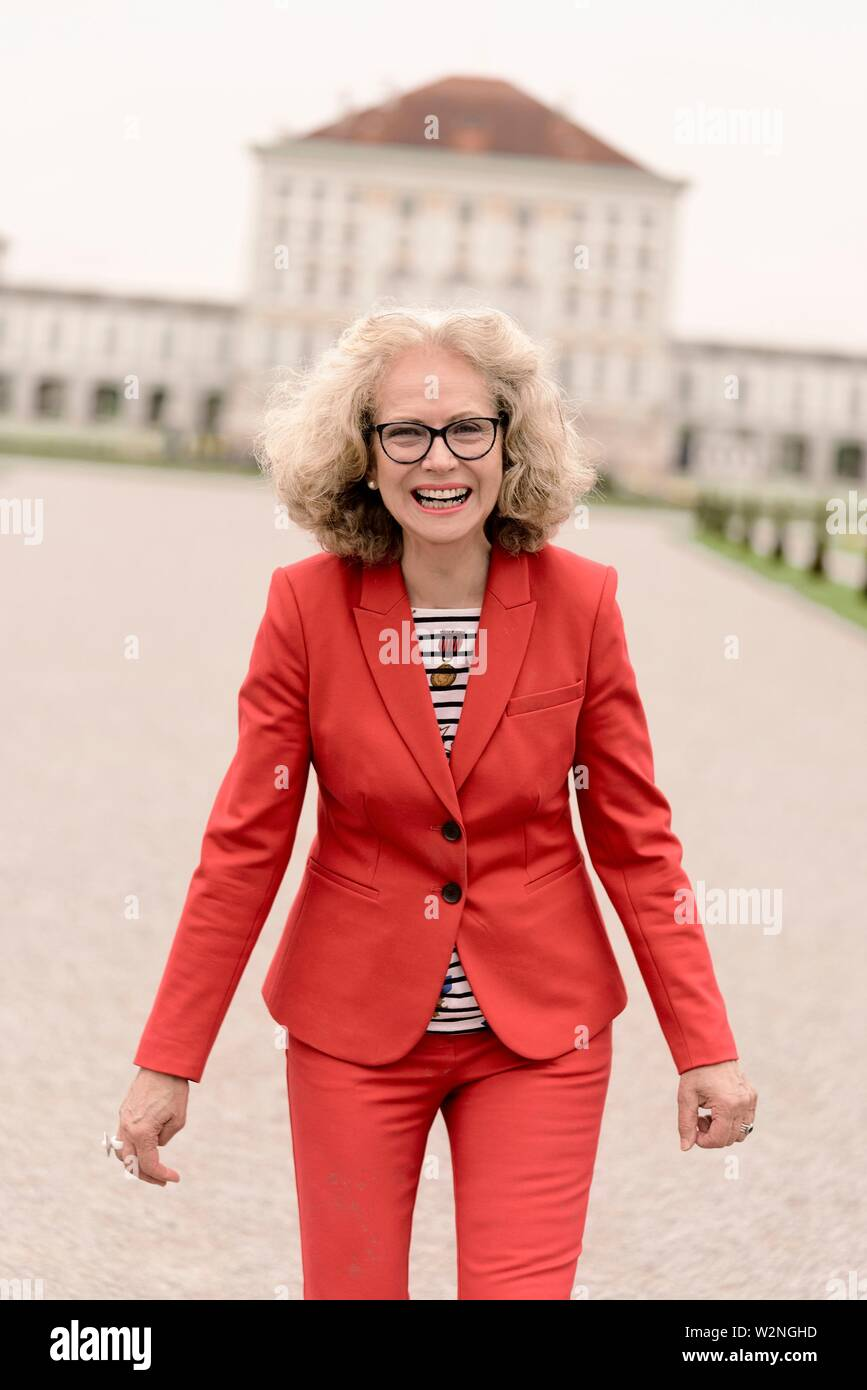 lively senior woman (67 years old) at touristic sight Nymphenburg palace, in Munich, Germany. - Stock Image