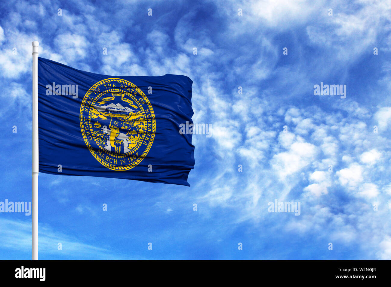 National flag State of Nebraska on a flagpole in front of blue sky - Stock Image