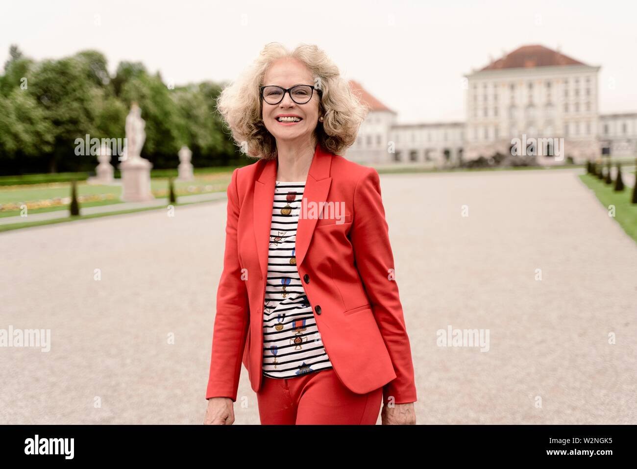 smiling senior woman (67 years old) in park at touristic sight Nymphenburg palace, in Munich, Germany. - Stock Image