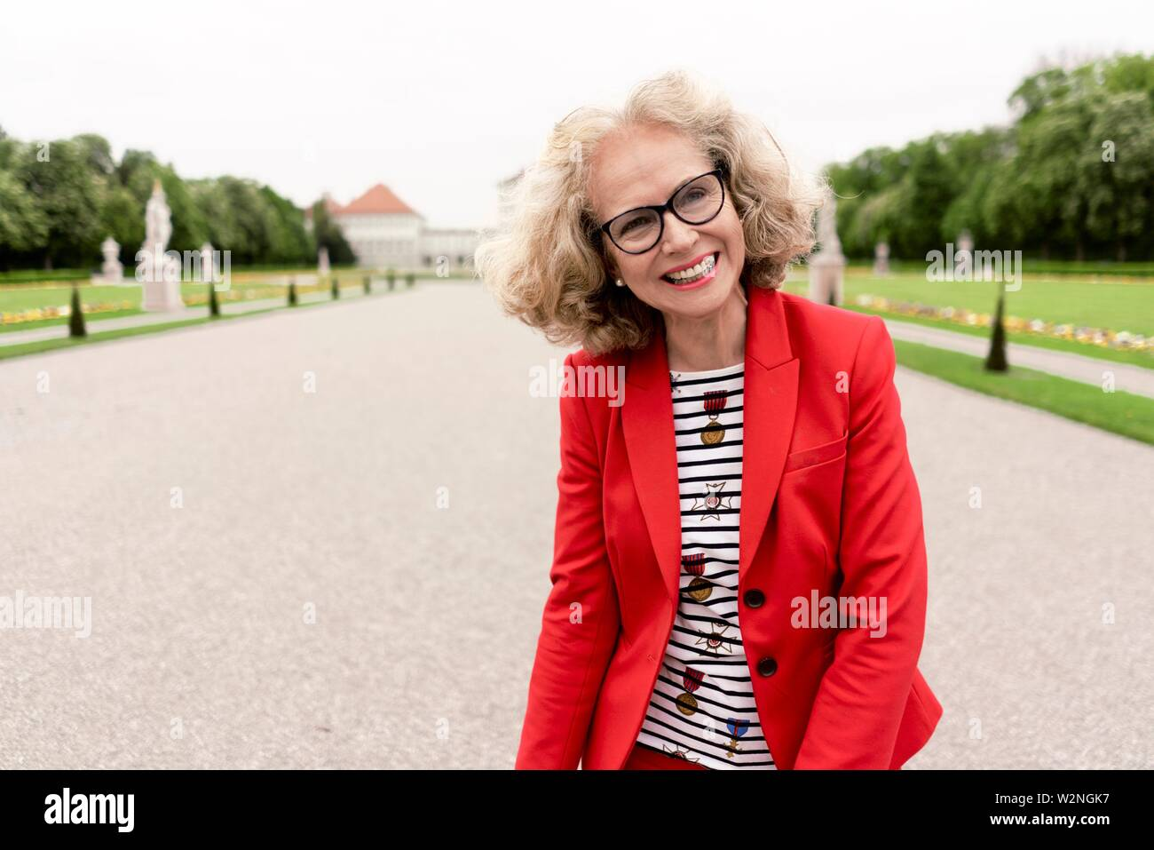 smiling senior woman (67 years old) in park, in Nymphenburg, Munich, Germany. Stock Photo