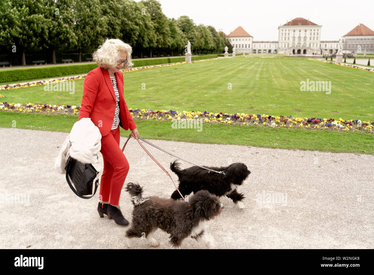 senior woman walking with two dogs in park at touristic sight Nymphenburg palace, in Munich, Germany. - Stock Image