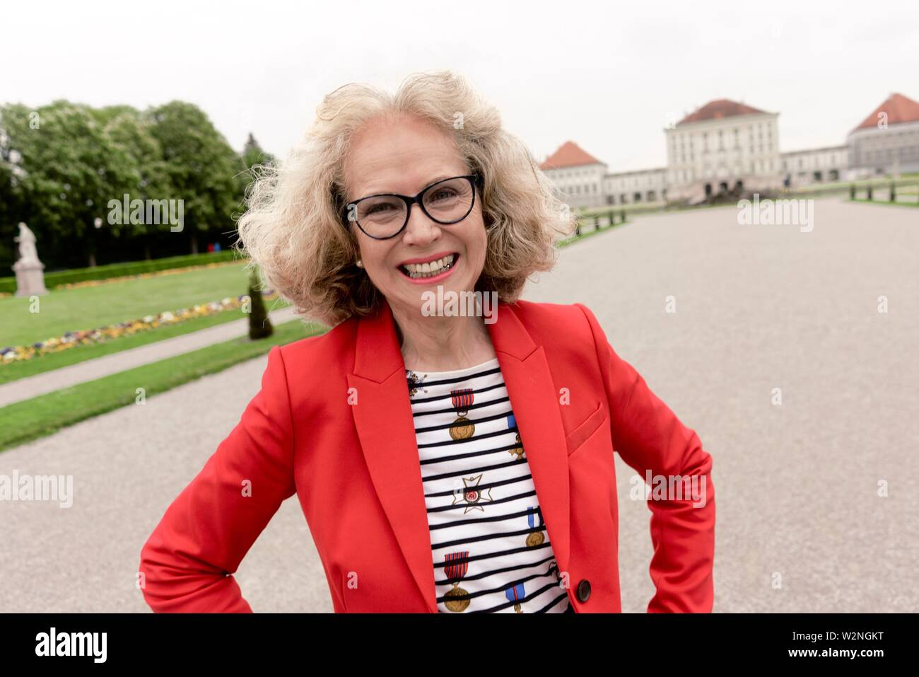 happy senior woman (67 years old) in park next to touristic attraction Schloss Nympenburg, in Nymphenburg, Munich, Germany. - Stock Image