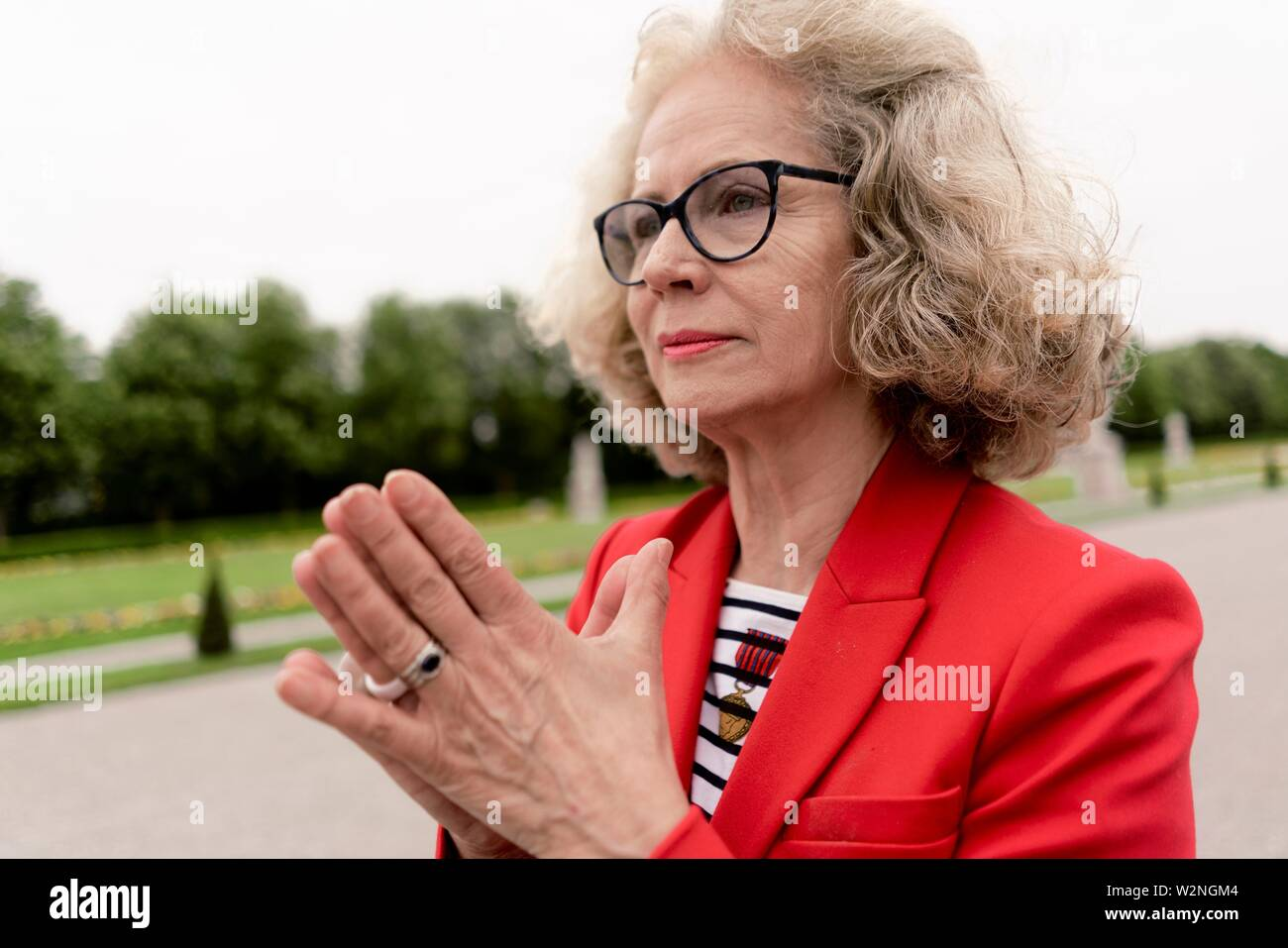 senior woman (67 years old) with folded hands in park, in Nymphenburg, Munich, Germany. - Stock Image