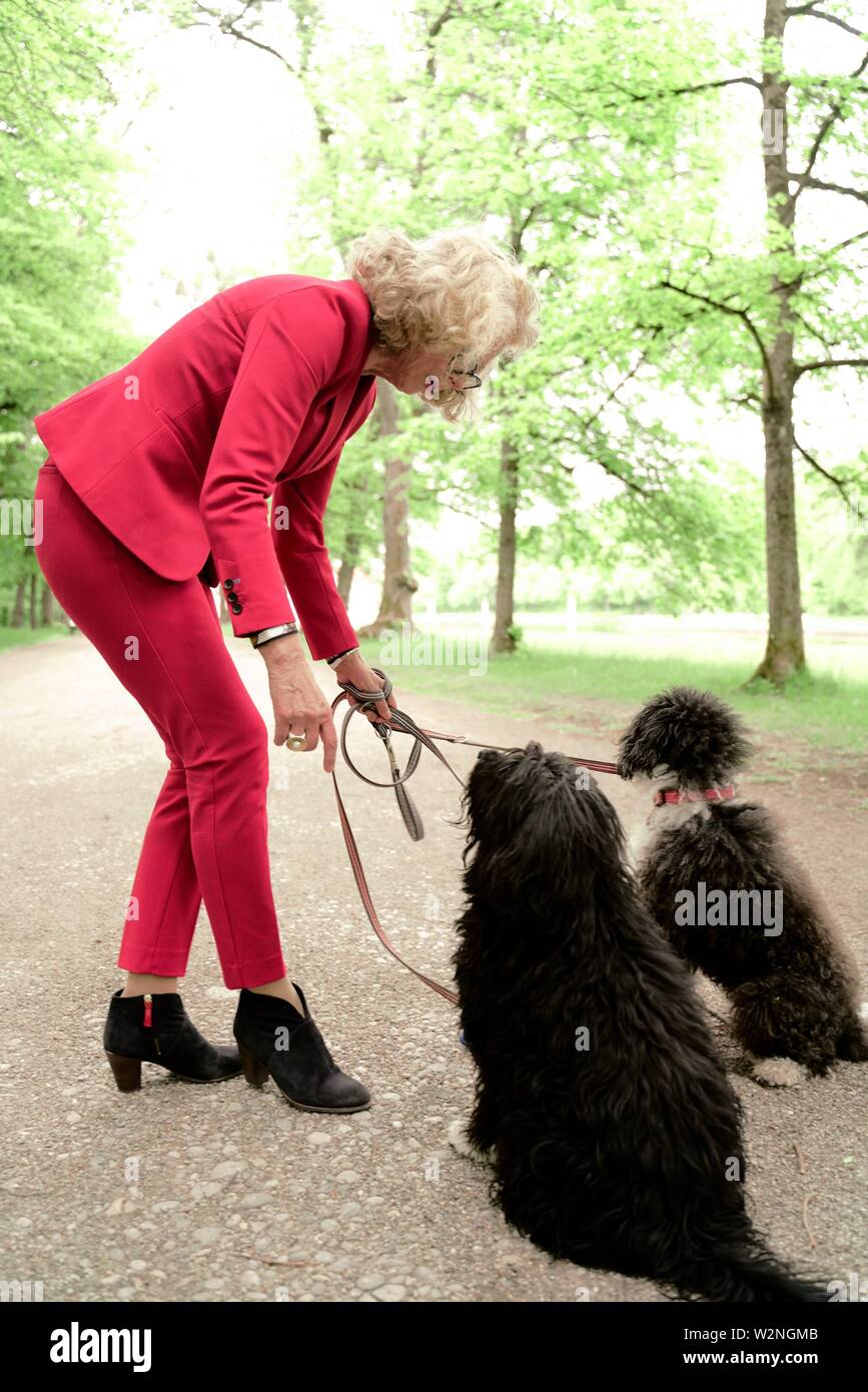 senior woman (67 years old) with her two dogs on leash in park, in Nymphenburg, Munich, Germany. - Stock Image