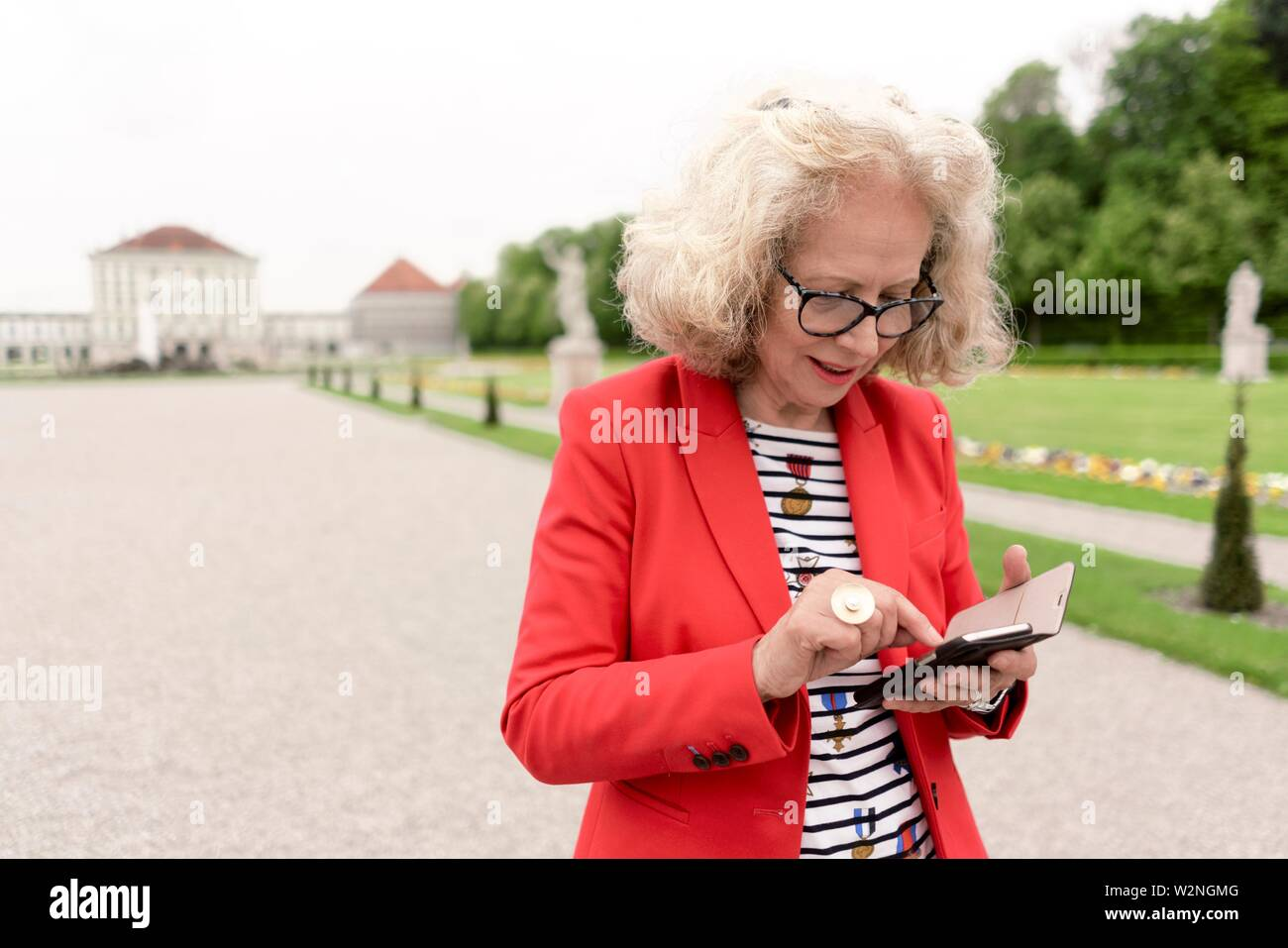 senior woman (67 years old) typing message with smartphone in park at touristic sight Nymphenburg palace, in Munich, Germany. - Stock Image