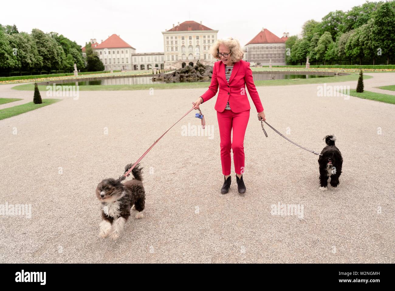 senior woman (67 years old) with dogs on leash at touristic sight Nymphenburg palace, in Munich, Germany. - Stock Image