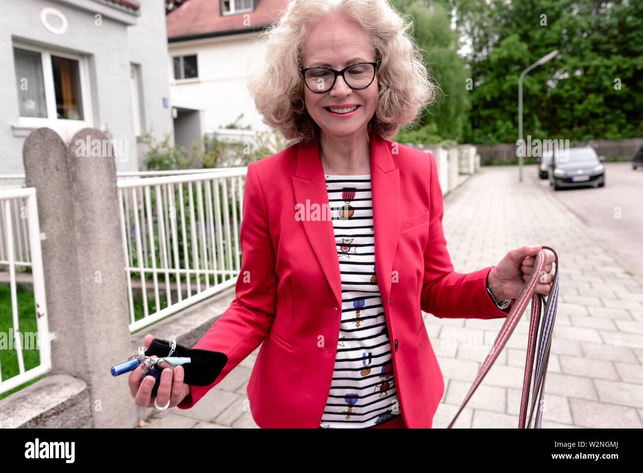 senior woman (67 years old) with dog leash and house keys in residential district, in Nymphenburg, Munich, Germany. - Stock Image