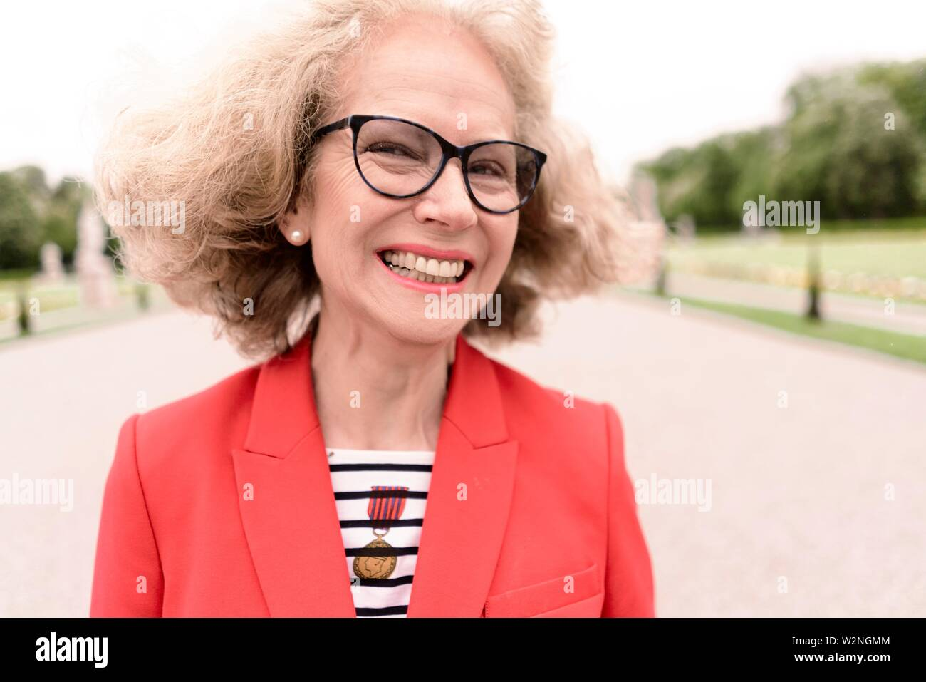 lively senior woman (67 years old) in park, in Nymphenburg, Munich, Germany. - Stock Image