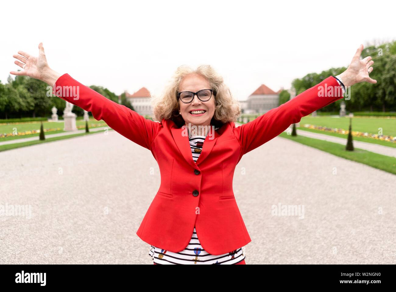 happy senior woman (67 years old) stretching arms in park at touristic sight Nymphenburg palace, in Munich, Germany. - Stock Image