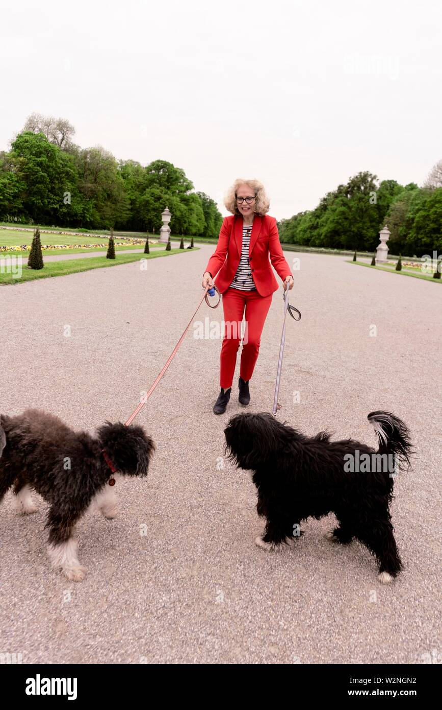 senior woman (67 years old) with two dogs in park, in Nymphenburg, Munich, Germany. - Stock Image