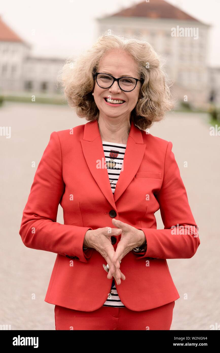 sanguine senior woman (67 years old) at touristic sight Nymphenburg palace, in Munich, Germany. - Stock Image
