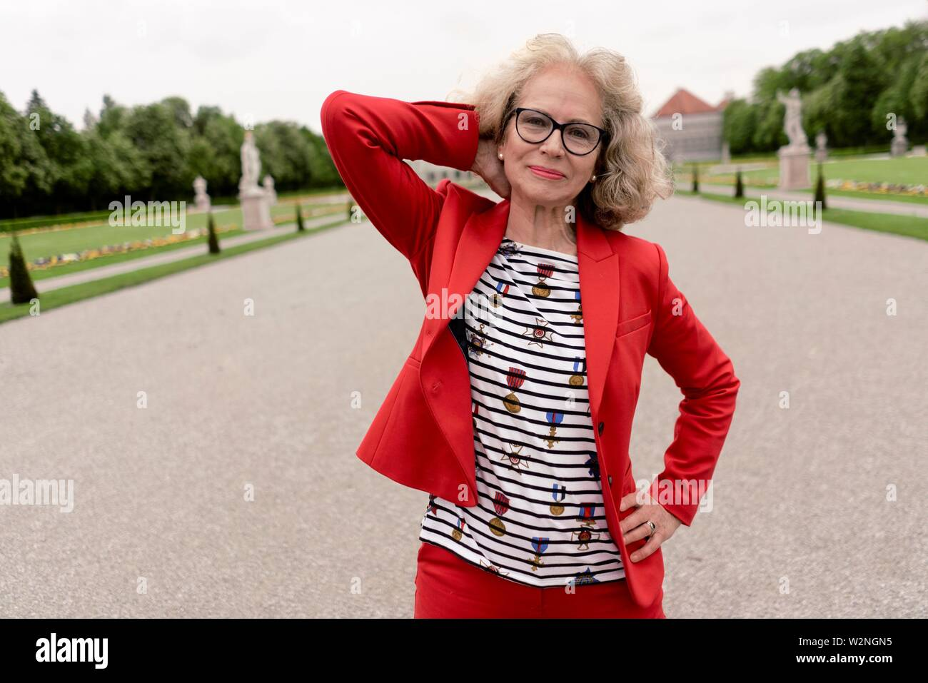 content senior woman (67 years old) outdoors in park, in Nymphenburg, Munich, Germany. - Stock Image