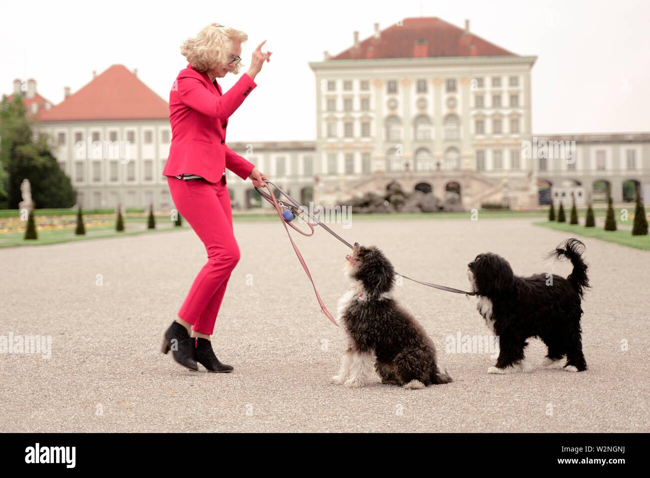 senior woman (67 years old) commanding her two dogs to sit down in park at touristic sight Nymphenburg palace, Munich, Germany. - Stock Image