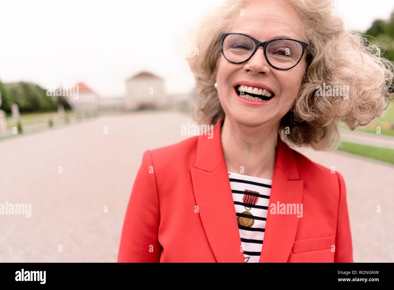happy senior woman (67 years old) laughing in park at touristic sight Nymphenburg palace, in Munich, Germany. - Stock Image