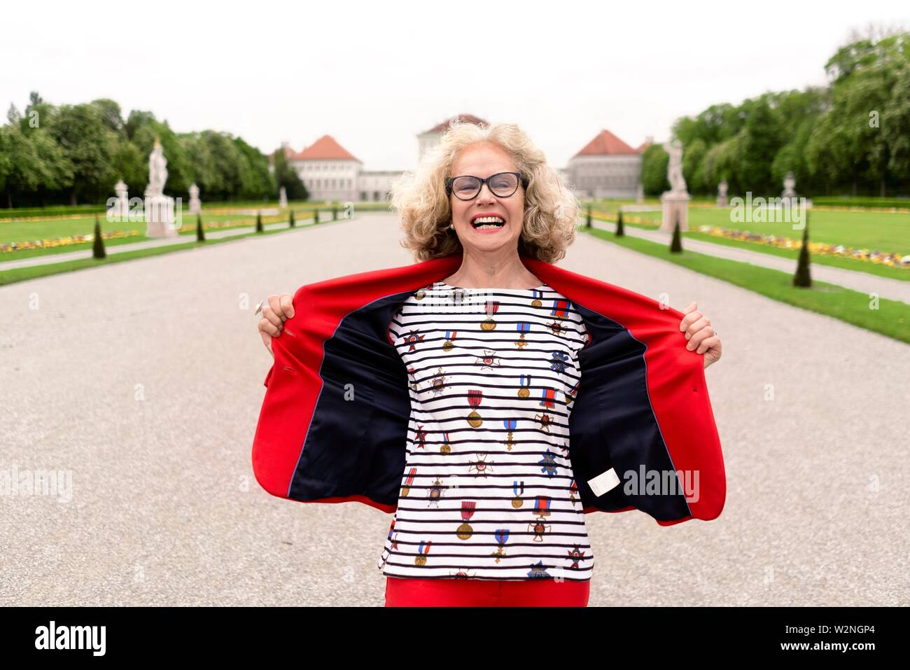 happy extrovert senior woman (67 years old) in park at touristic sight Nymphenburg palace, in Munich, Germany. - Stock Image