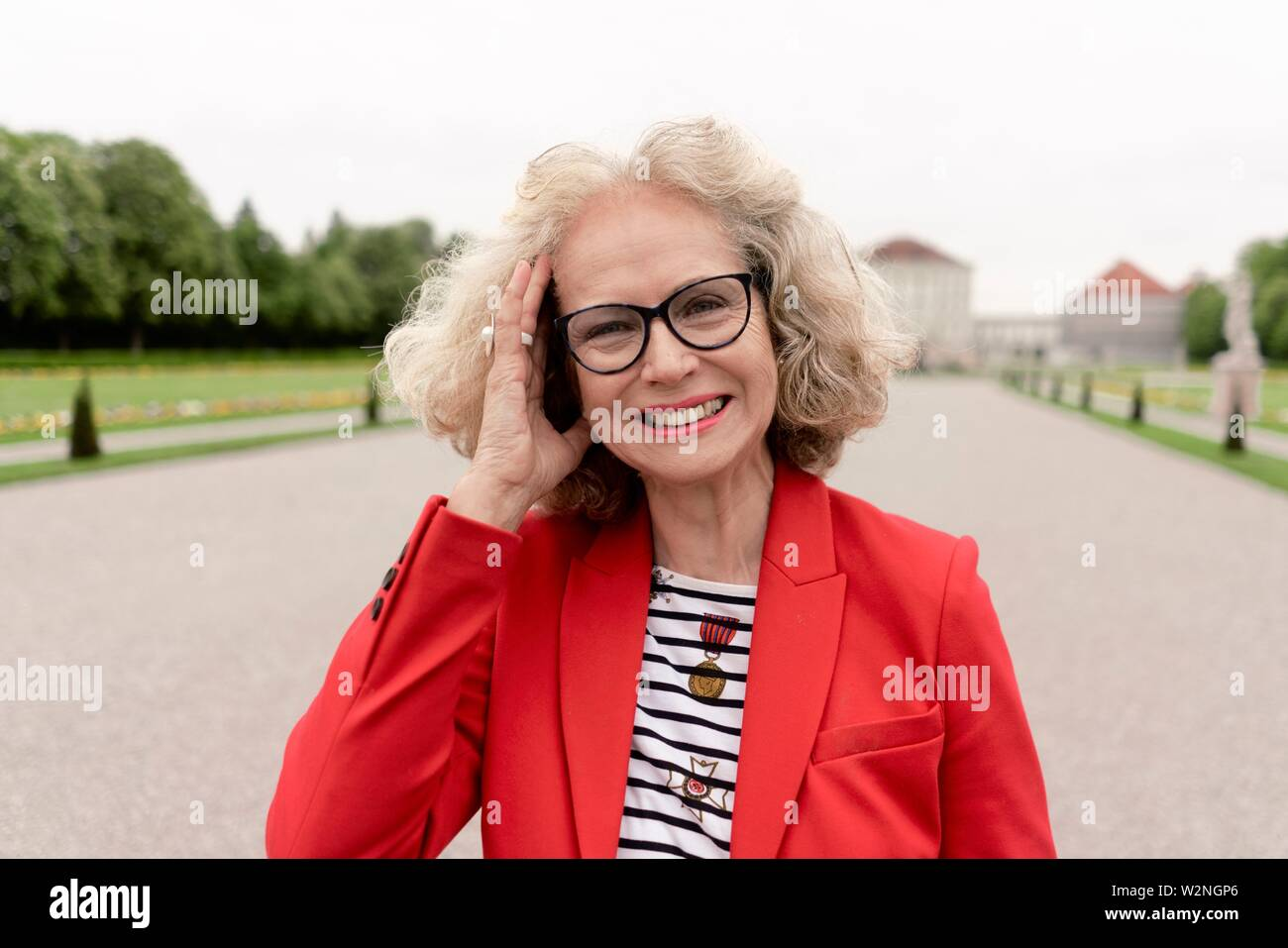 smiling senior woman (67 years old) with hand on head in park, in Nymphenburg, Munich, Germany. - Stock Image