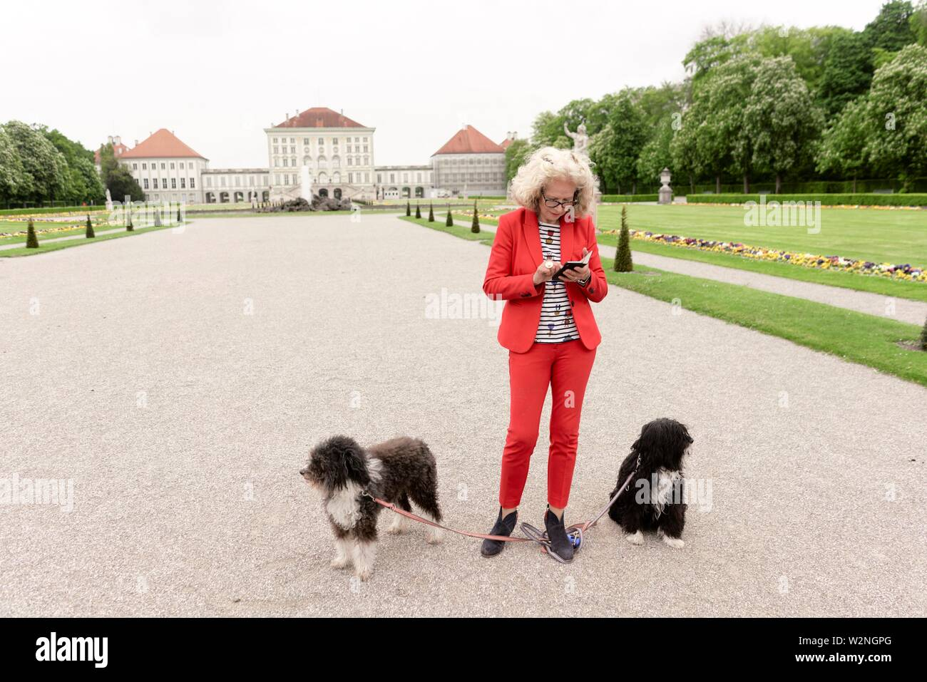 senior woman (67 years old) with two dogs in park, using smartphone at touristic sight Nymphenburg palace, in Munich, Germany. - Stock Image